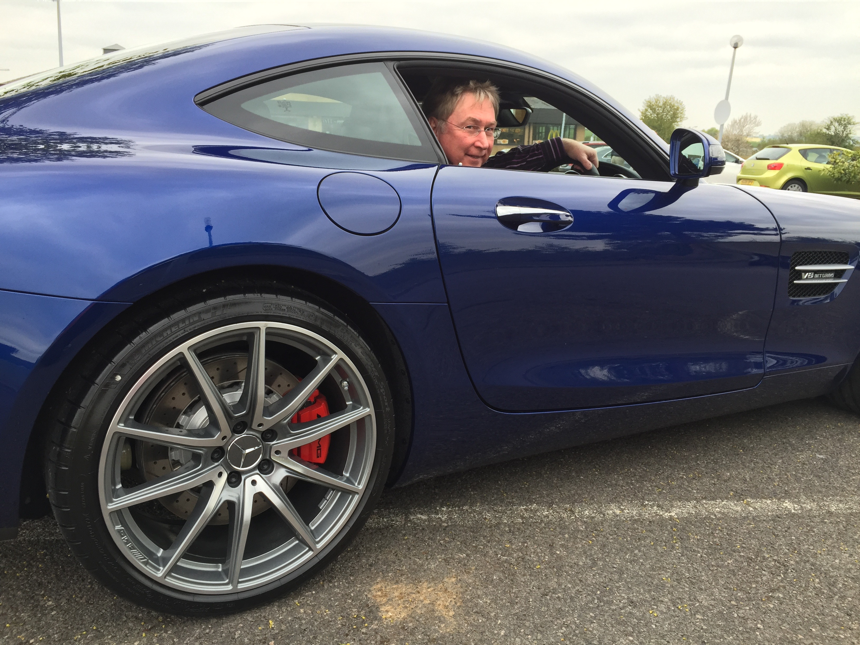 The author photographed sitting in a blue Mercedes AMG GT V8 powered sports car