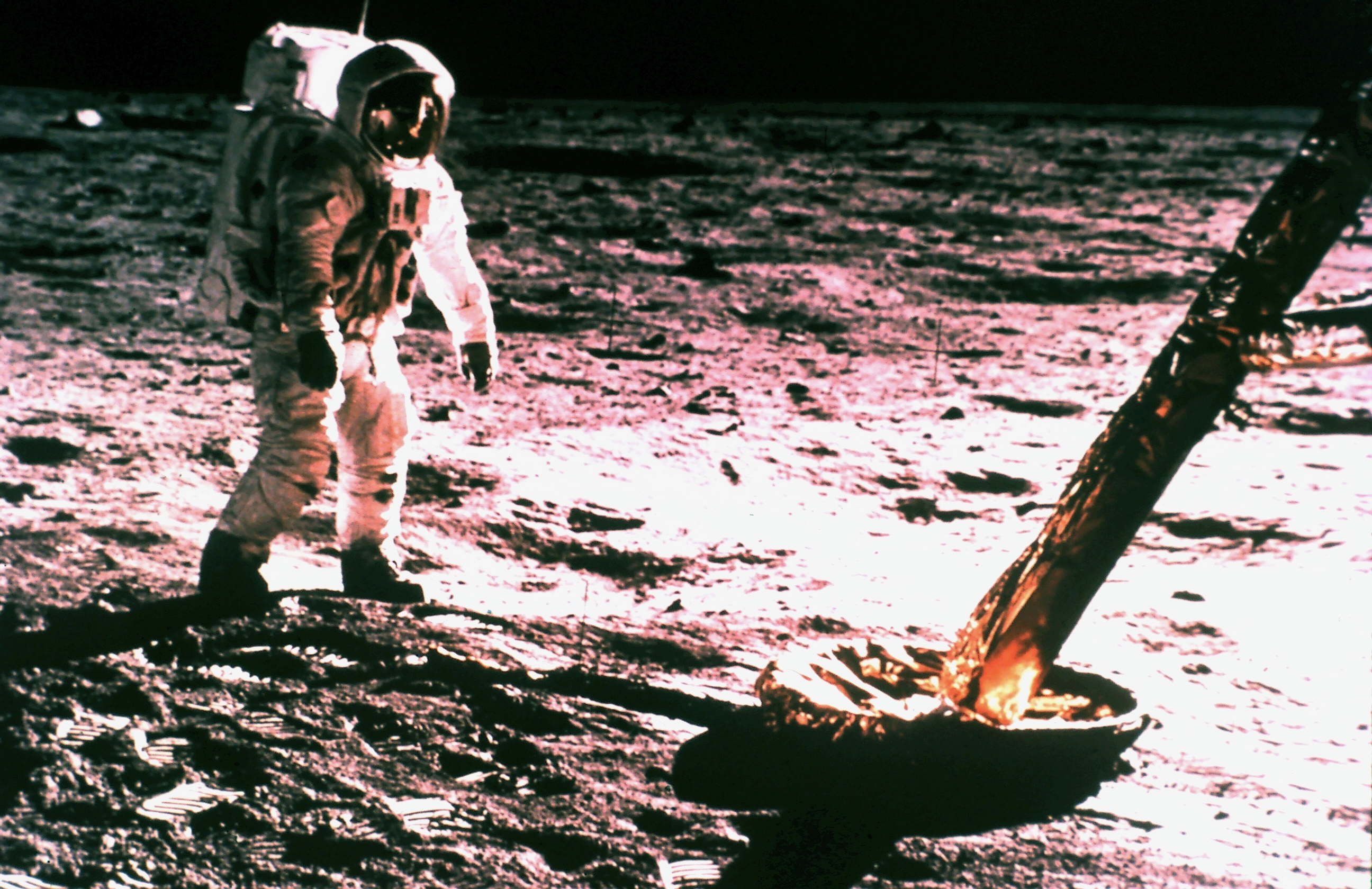An American astronaut stands in his white spacesuit and large glass fronted helmet on a rocky moon surface next to the foot of his lunar landing module