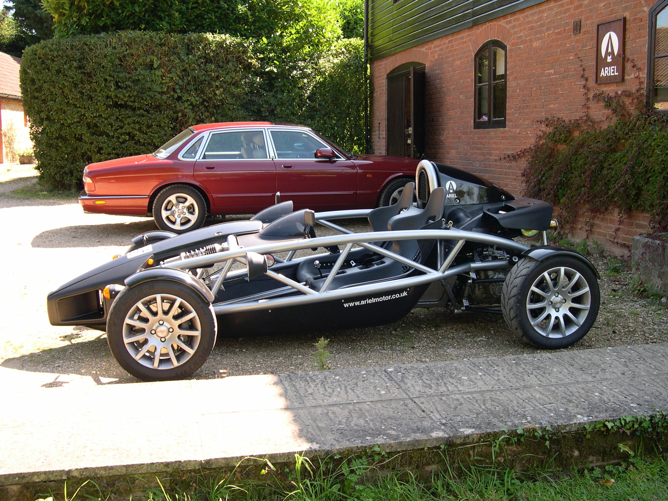 A black Ariel Atom stood in front of a red Jaguar XJ8