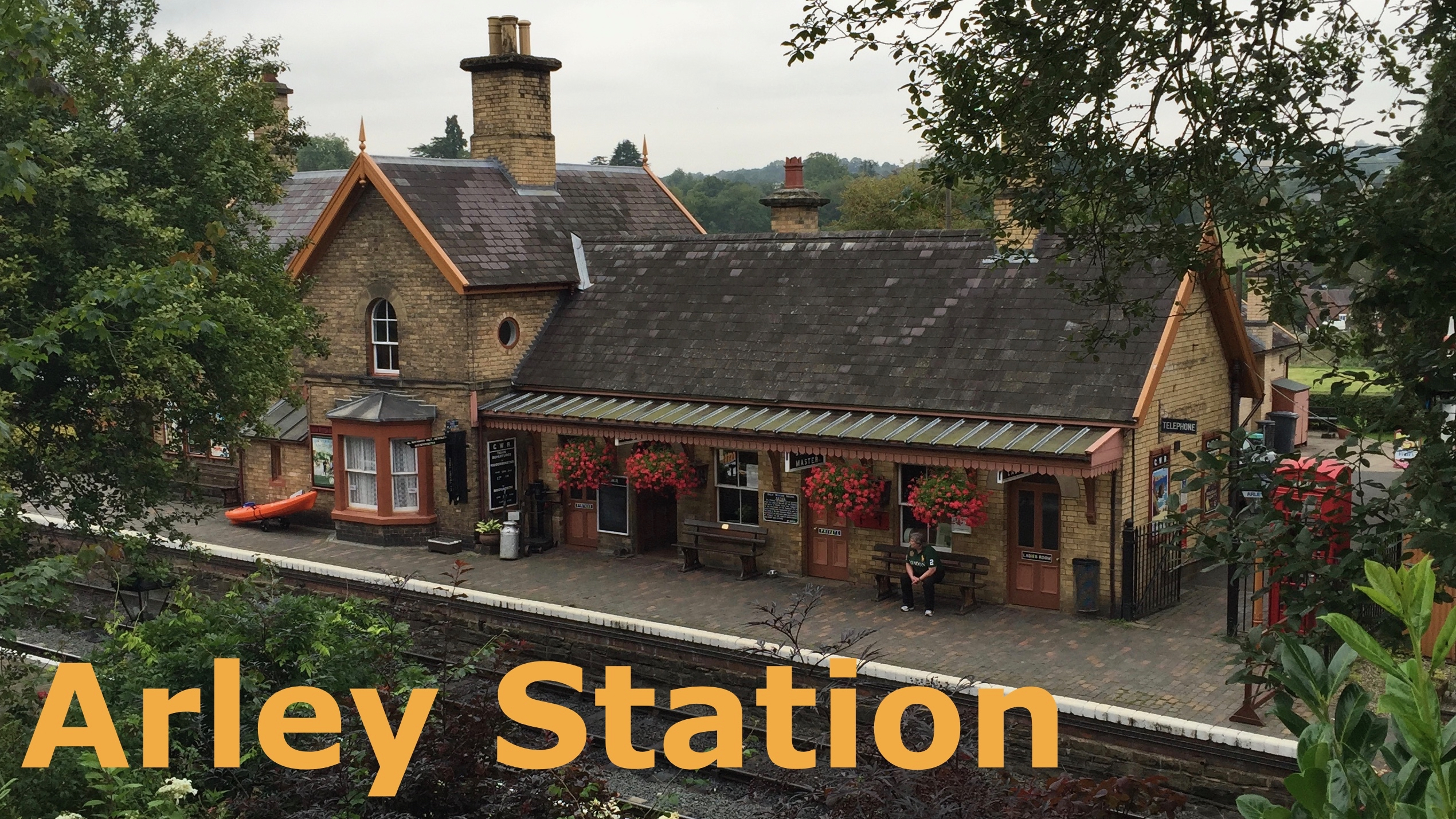 A  classic brick built railway station with high pitched roof and many colourful hanging baskets in a wooded area