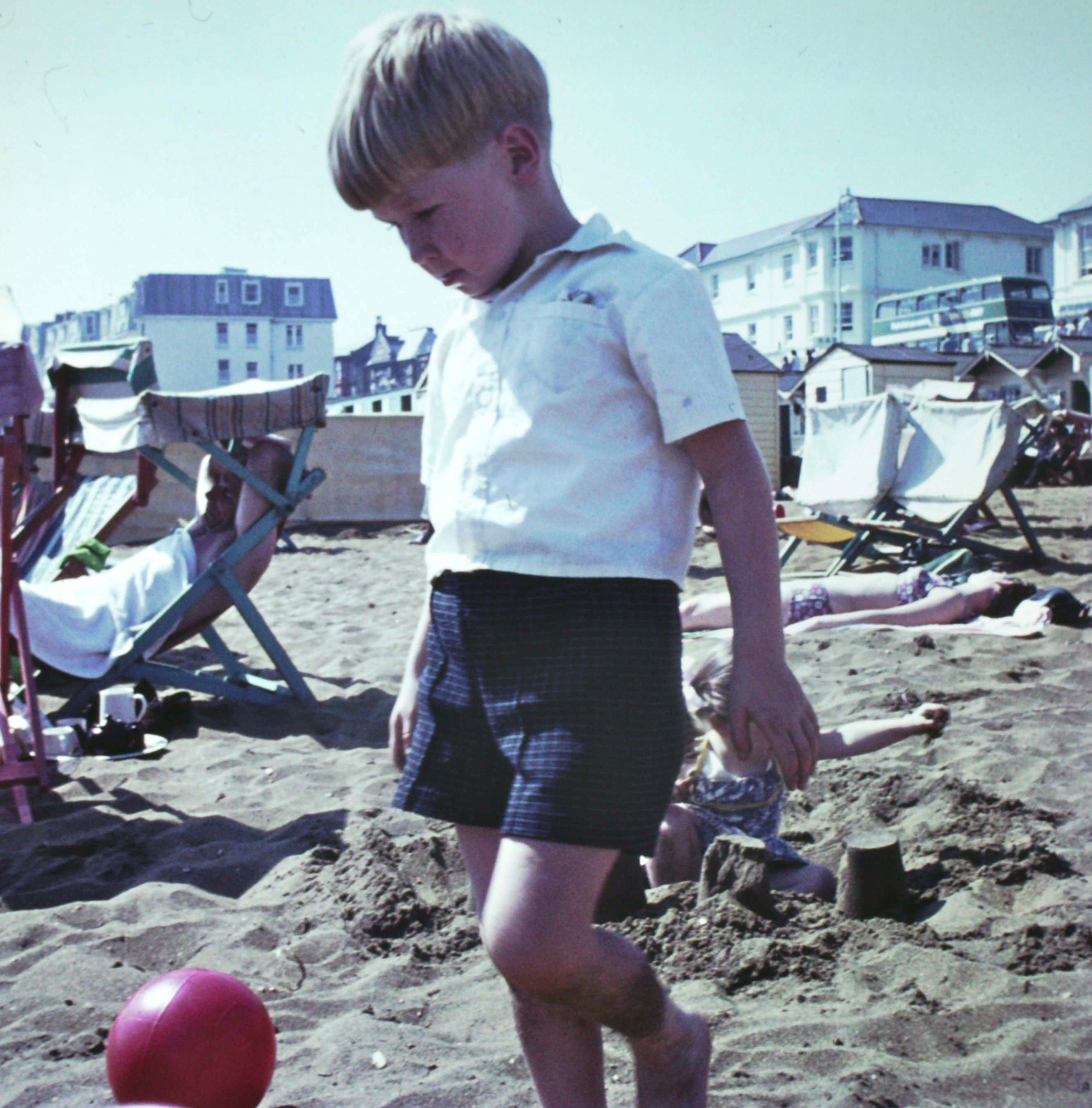 Photograph Vince, aged around six in shorts and white shirt on a sandy beach kicking a football