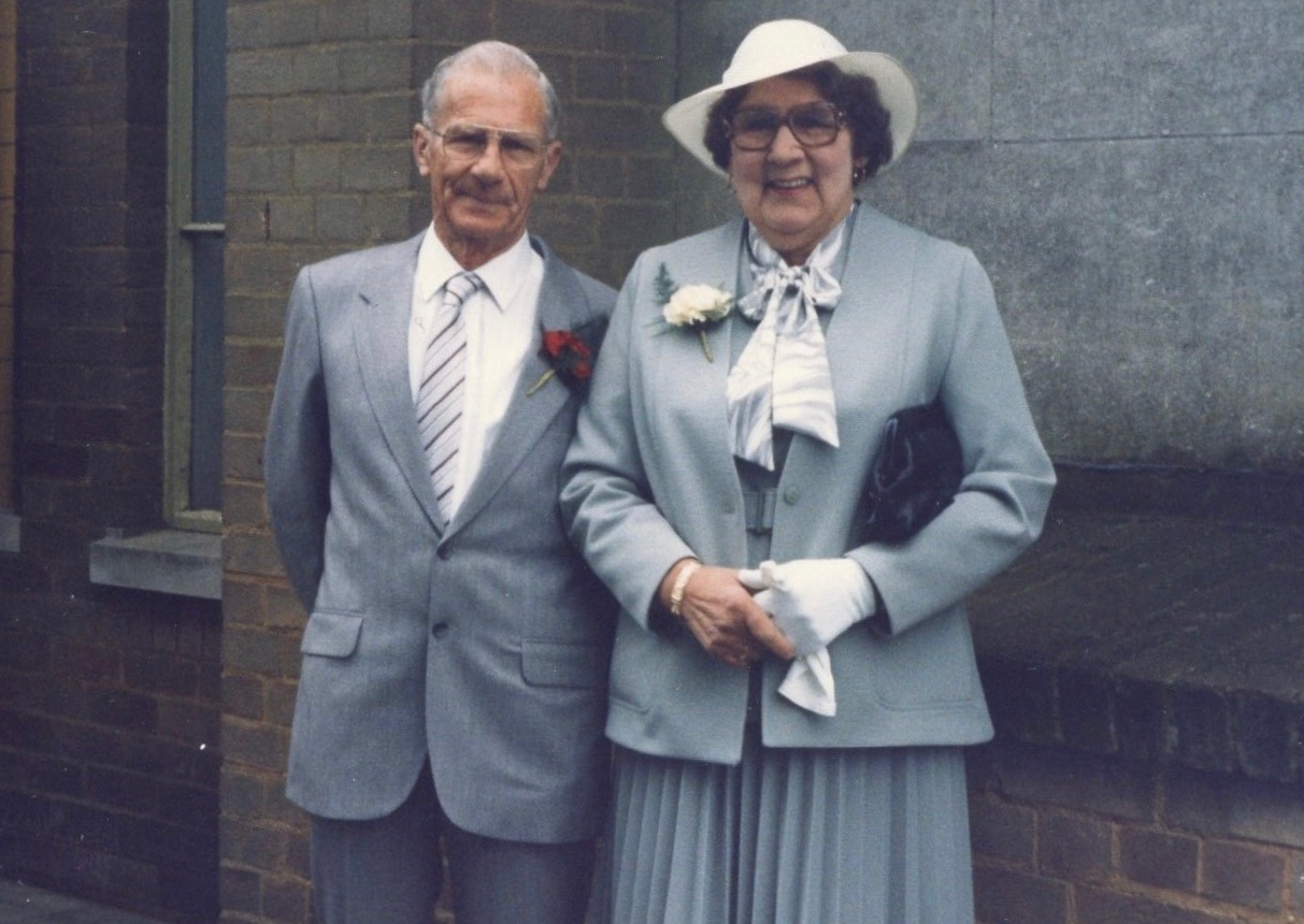 A photograph of the author's paternal grand-parents, stood, dressed formally for a wedding in matching light grey outfits