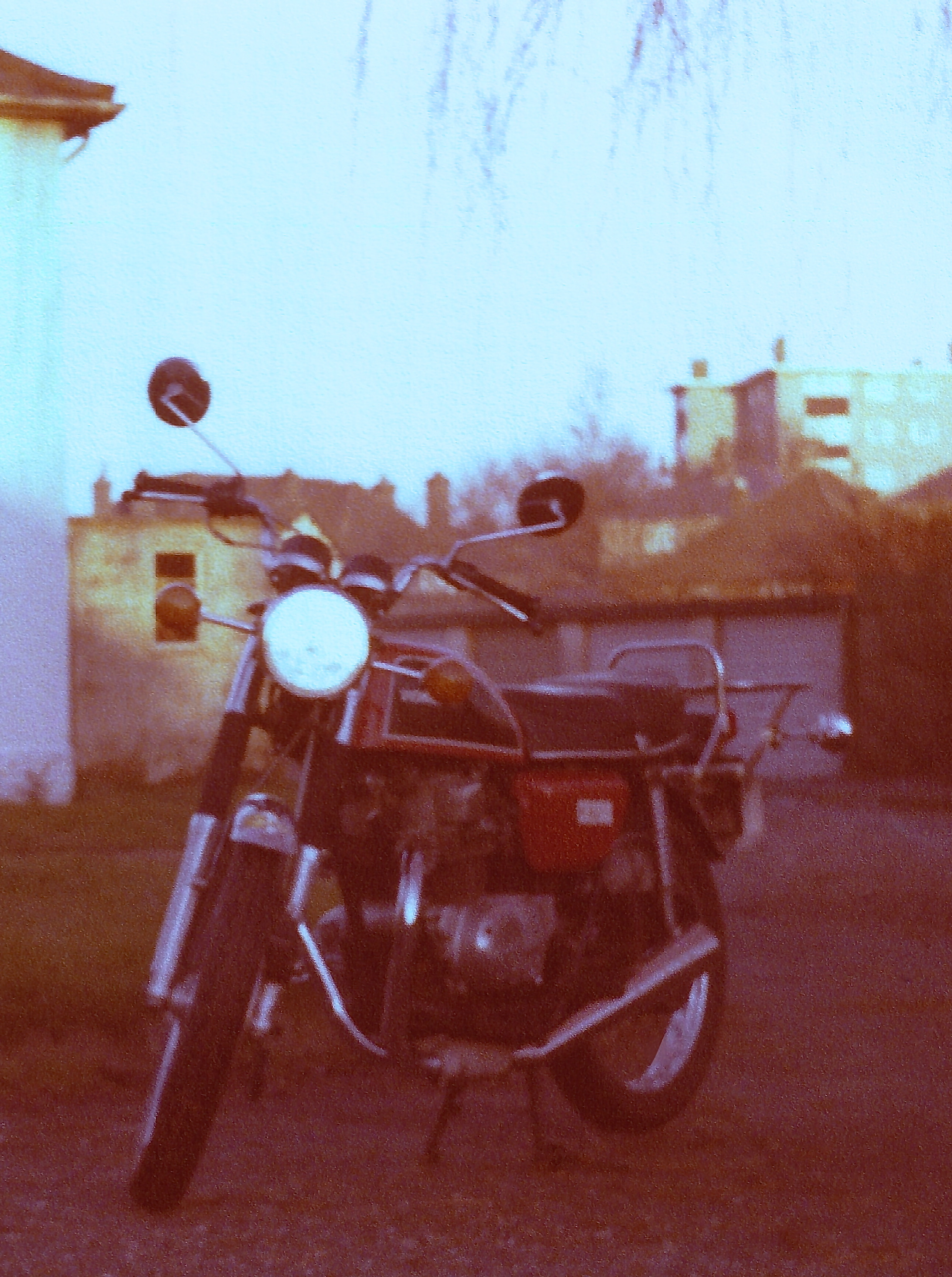 A red Honda CB200 with Cibie Hedlamp and replacement exhaust