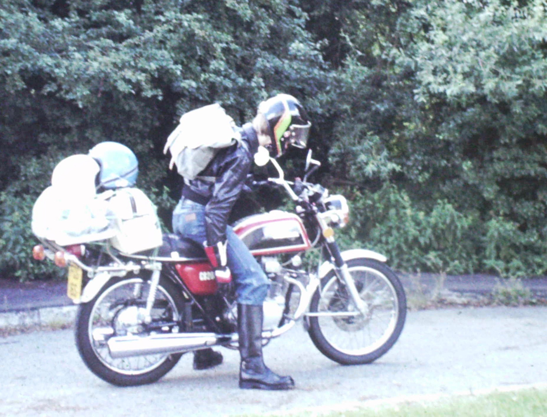 The author sat on his Honda CB200 which is loaded with huge bags and two spare helmets