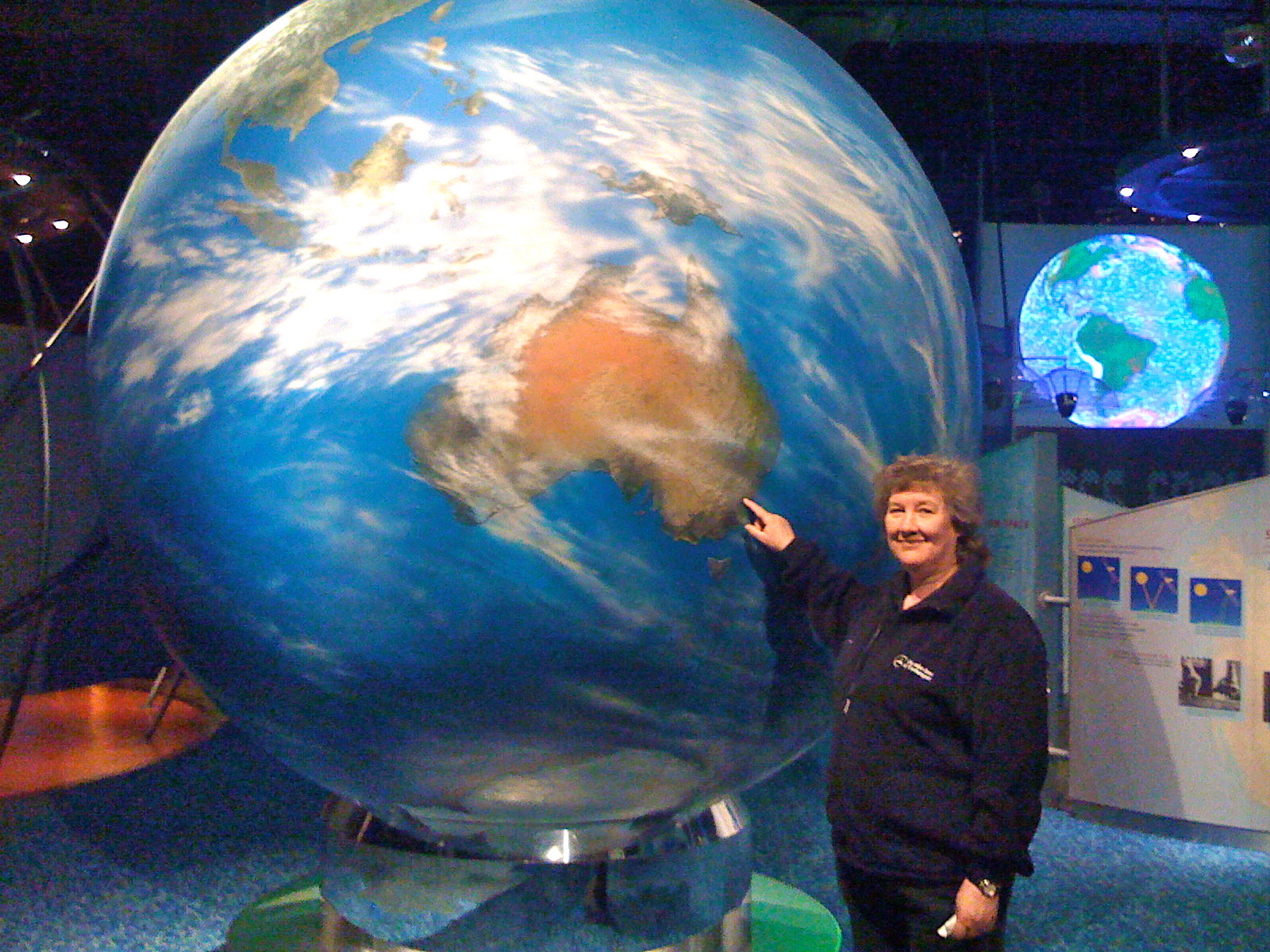 Photograph of Lynda pointing out Australia on a large globe