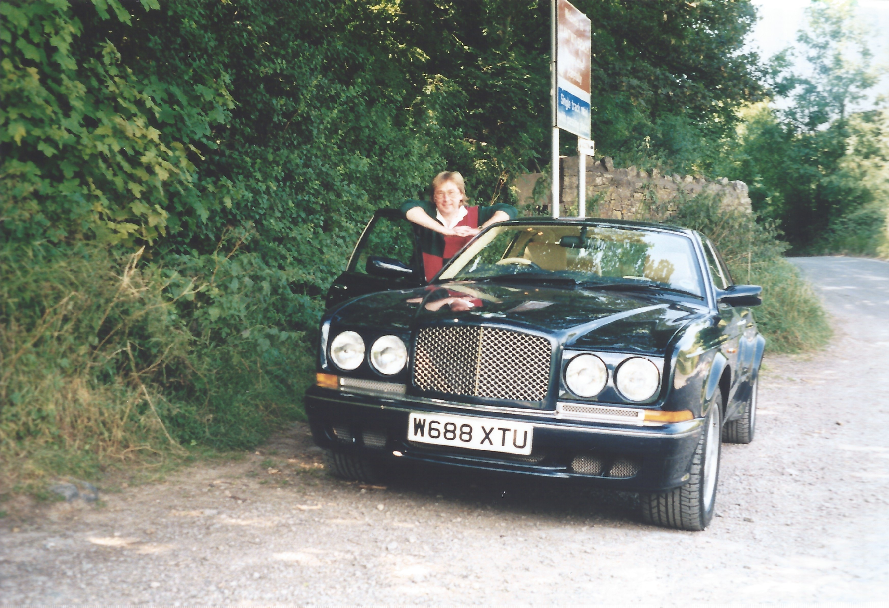 The author stood in the open doorway of a dark blue Bentley Continental