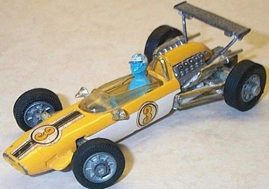 Photograpgh of a slightly tatty yellow and white Cooper racing car with steering operated from a leaning driver and a high rear wing