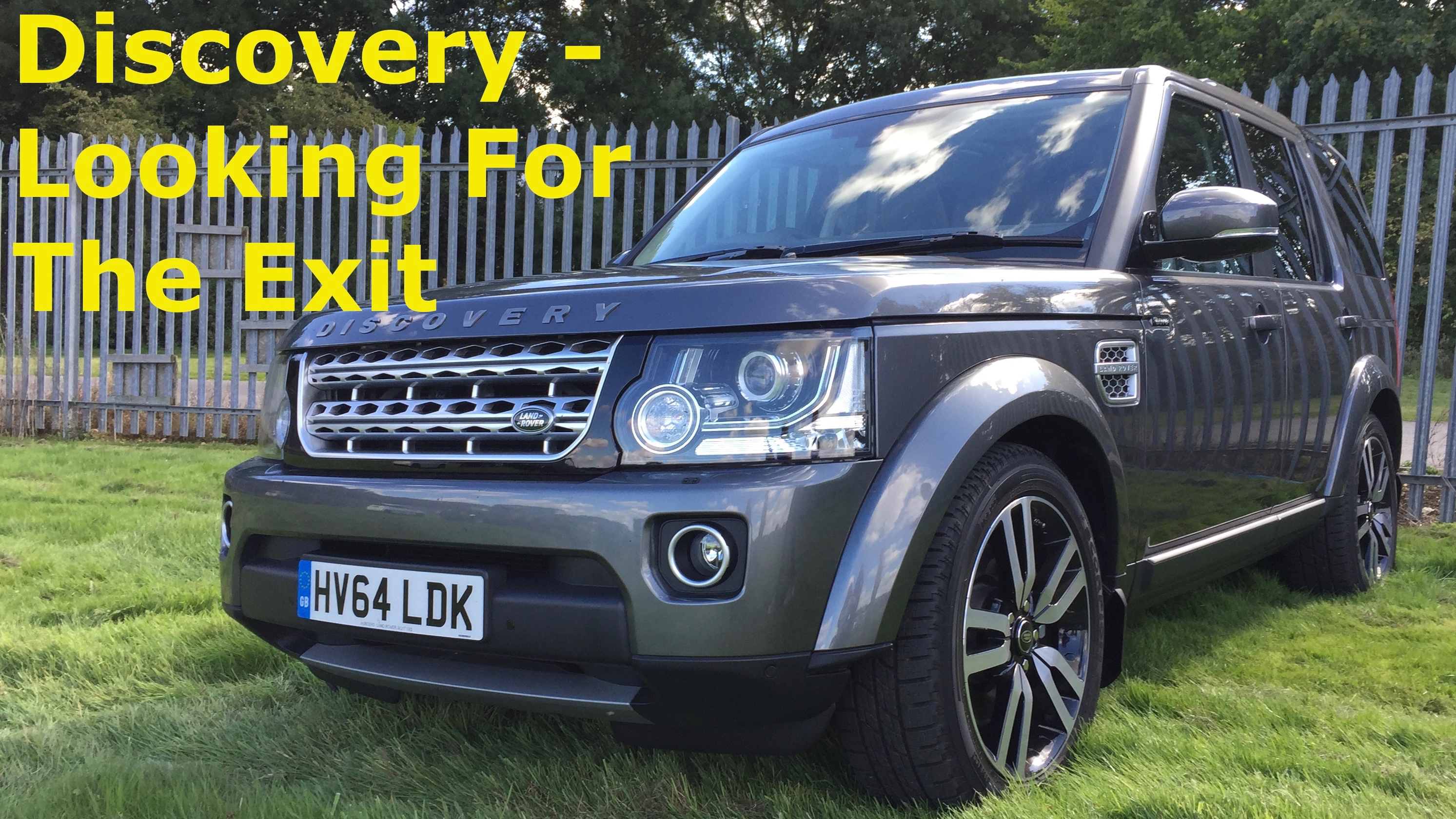 A  grey Land Rover Discovery mark 4 facelift parked in a grassy field next to some galvanised security fencing with the title in yellow reading Discovery - Looking For The Exit