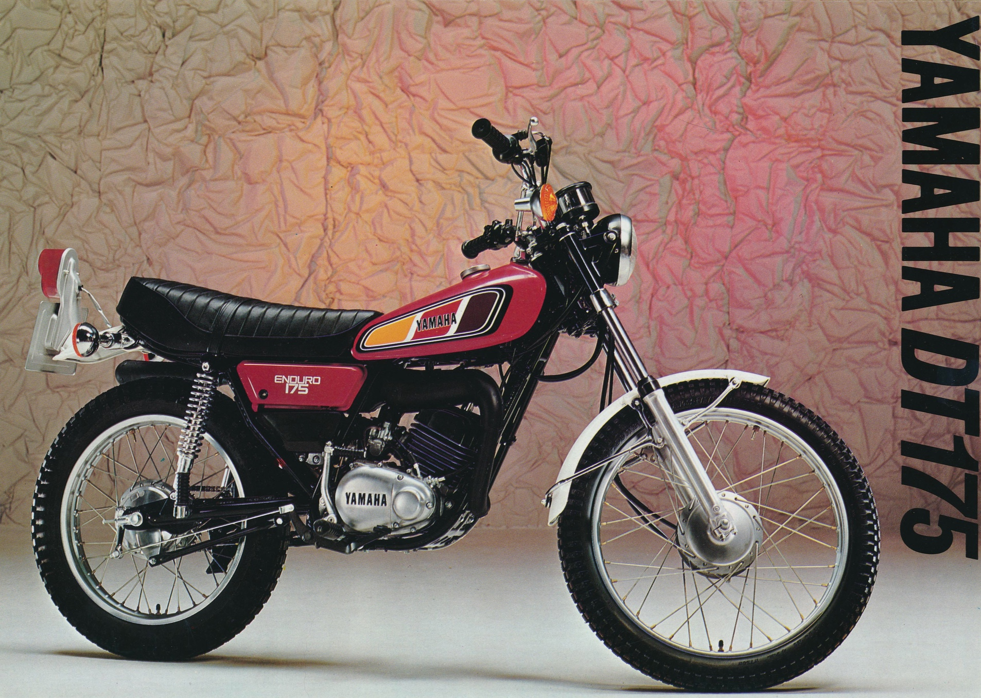 A red Yamaha DT175 trails style motorcycle with the wording Yamaha DT175 written vertically on the right from the front cover of a sales brochure