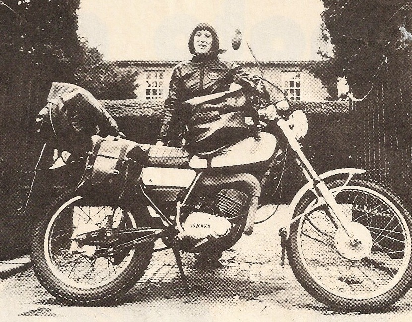 Black and white photograph of a leather clad female motorcyclist stood behind her Yamaha DT175 motorcycle which is laden with touring accessories