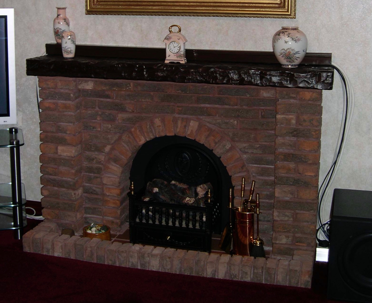 A pretty red brick hand-built classic fireplace with electric fire and substantial dark wood mantlepiece, set in a lounge with thick maroon carpet.  The fireplace is flanked by a flat screen TV and sub-woofer and has three pink and white mantle pots and matching carriage clock