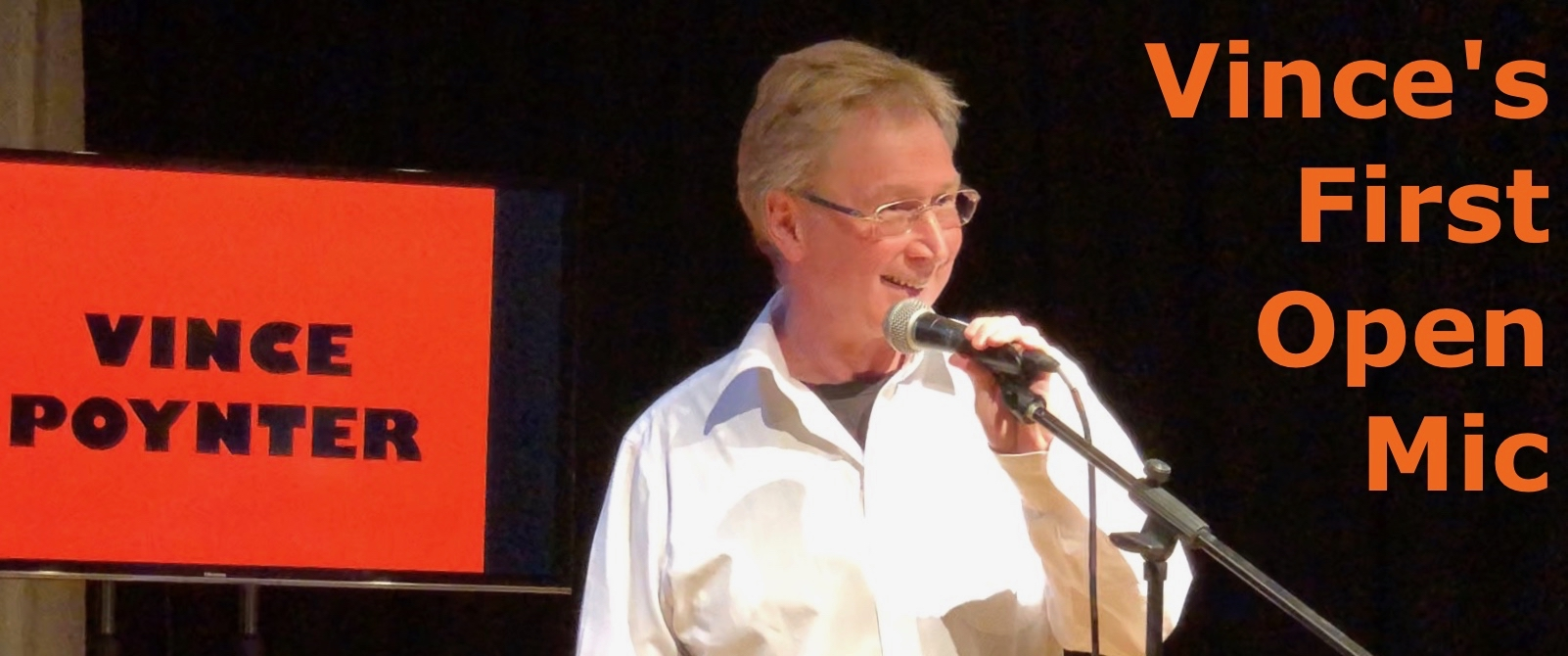 Image of a grinning Vince in a white shirt over a black tee-shirt performing his first open mic stand up routine using a stand mounted microphone. A large video display behind Vince shows his name, Vince Poynter, in bold black lettering on a red background. The room is otherwise dark.