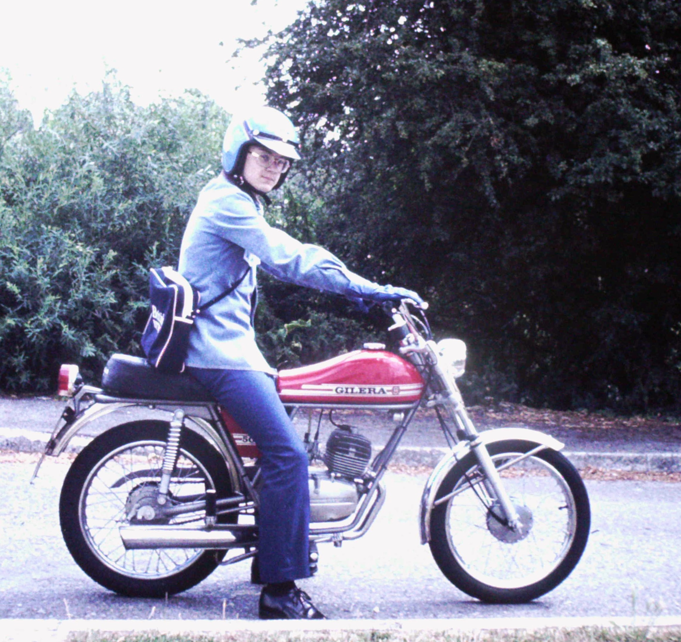 My double denim clad brother Mark sat astride his red Gilera 50 moped wearing a white open faced helmet and with a white sports bag over his shoulder