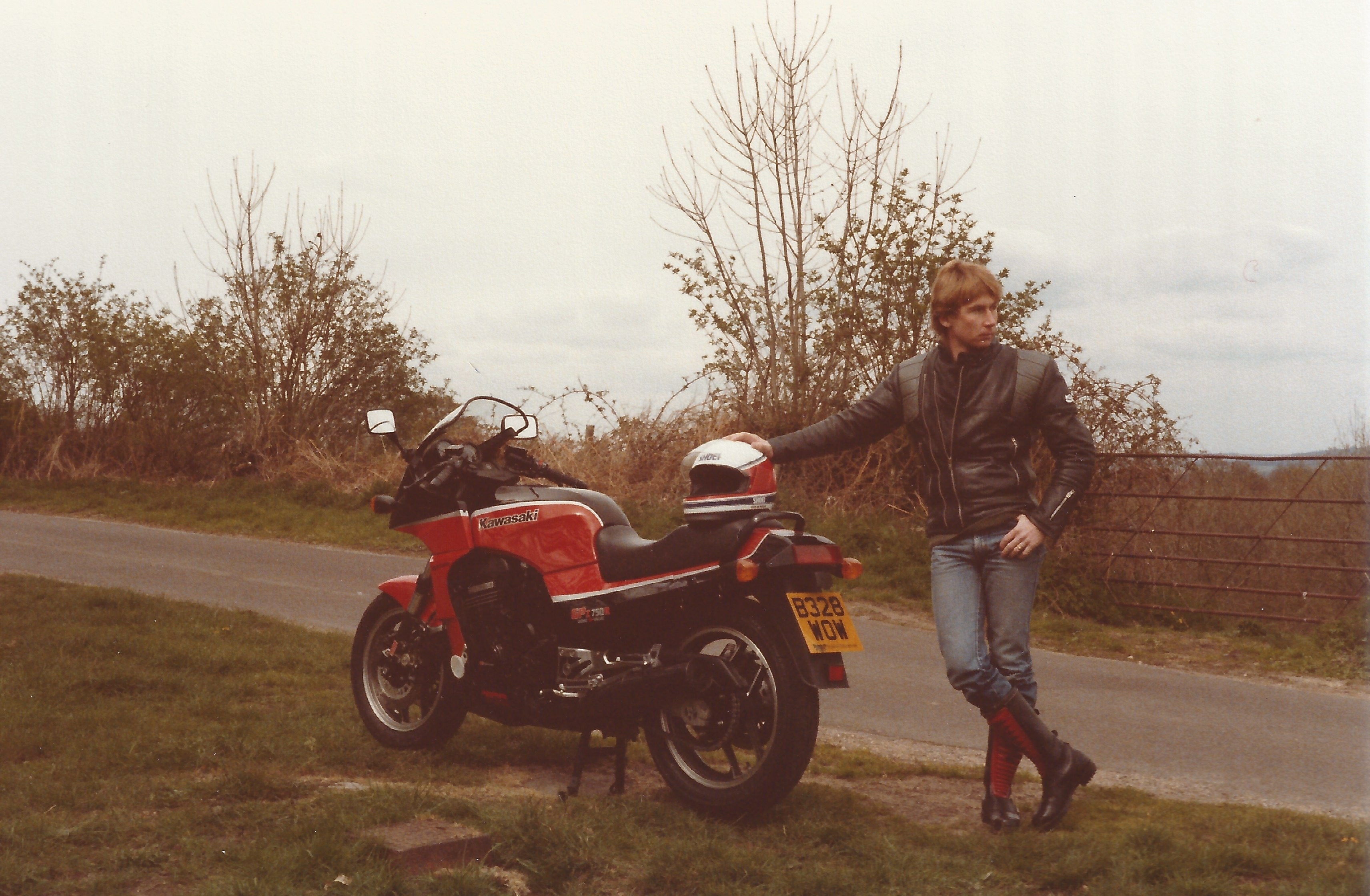 Vince Poynter, in full motorbike clothing and boots, standing at the rear of his black and red Kawasaki GPz750R motorcycle, which is stood on it's centre stand on a grass mound