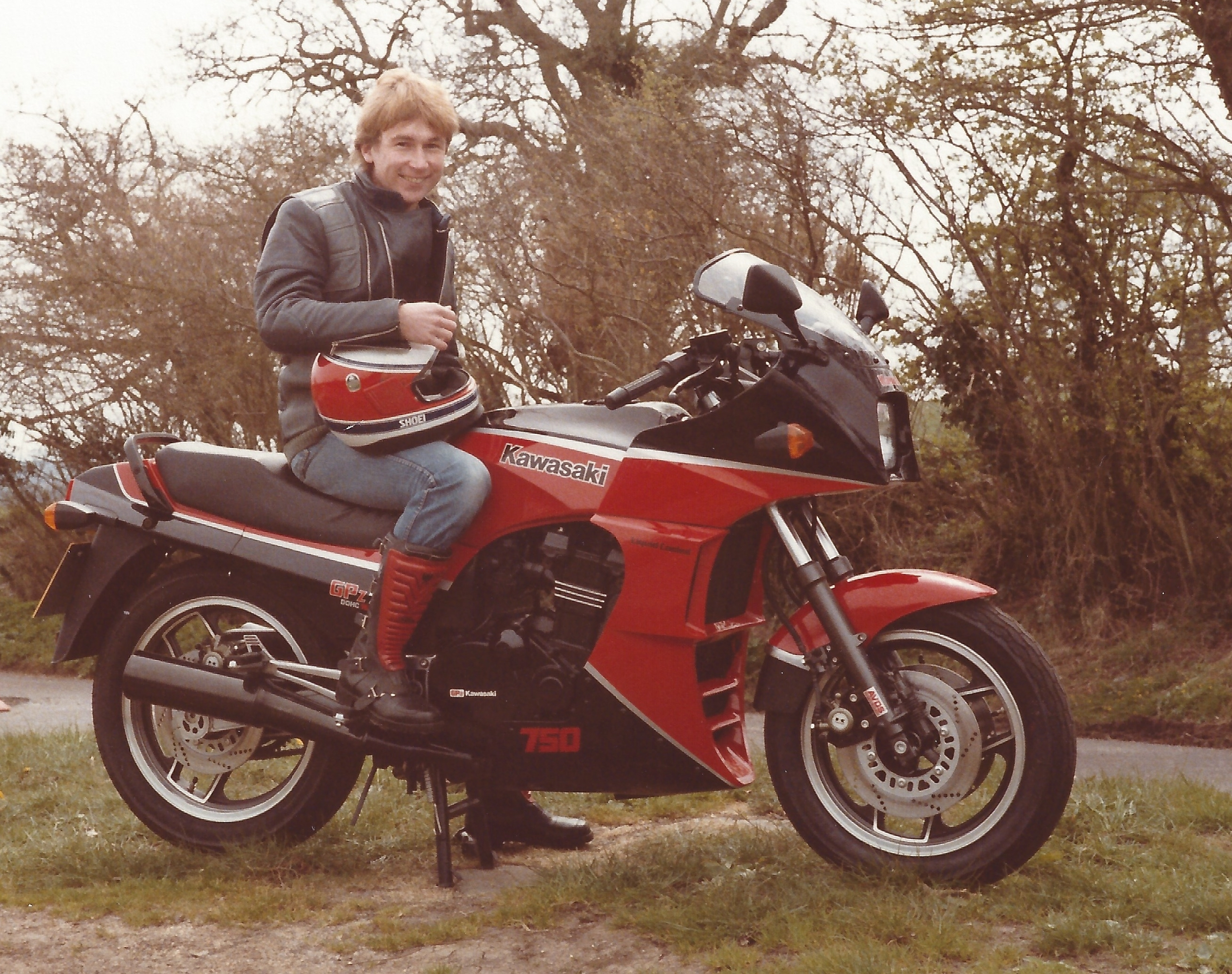 Vince Poynter, in full motorbike clothing and boots, sat on his black and red Kawasaki GPz750R motorcycle, which is stood on it's centre stand on a grass mound