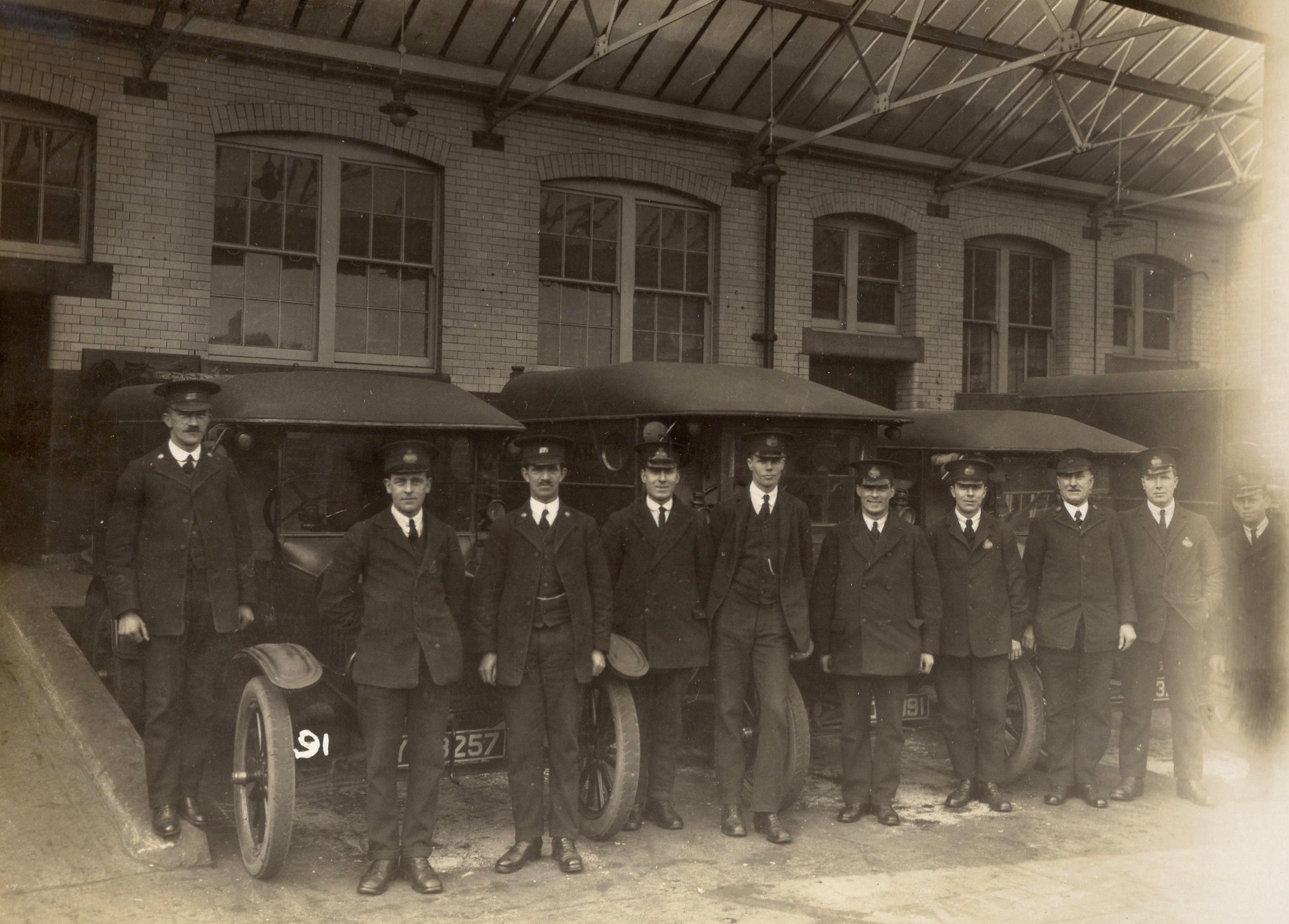 Sepia tone photograpgh showing Harry Poynter stood alongside a line of vintage post office vans and their drivers
