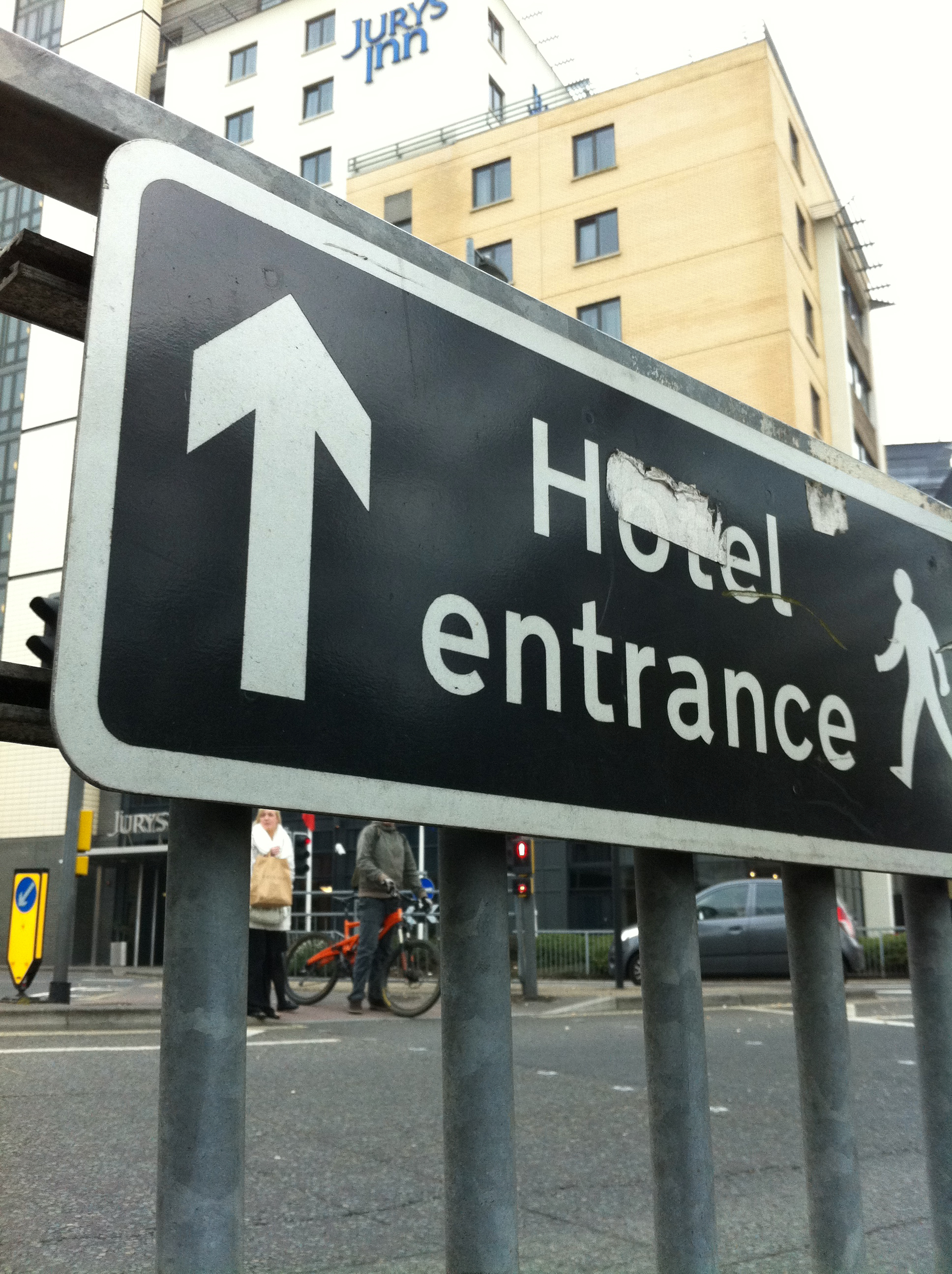 A sign attached to a railing at low level advising Hotel Entrance with a walking figurine and a vertically placed arrow. The photograph is taken from a low level showing the high rise Jurys Inn hotel in the background