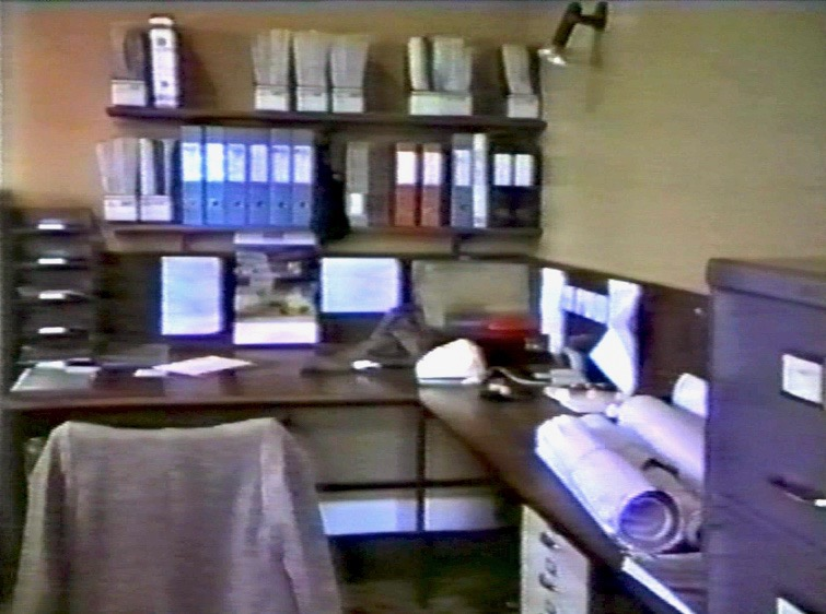 A photo of the author's busy wooden working desk showing a chair with jacket over the back, files, drawing rolls and telephone
