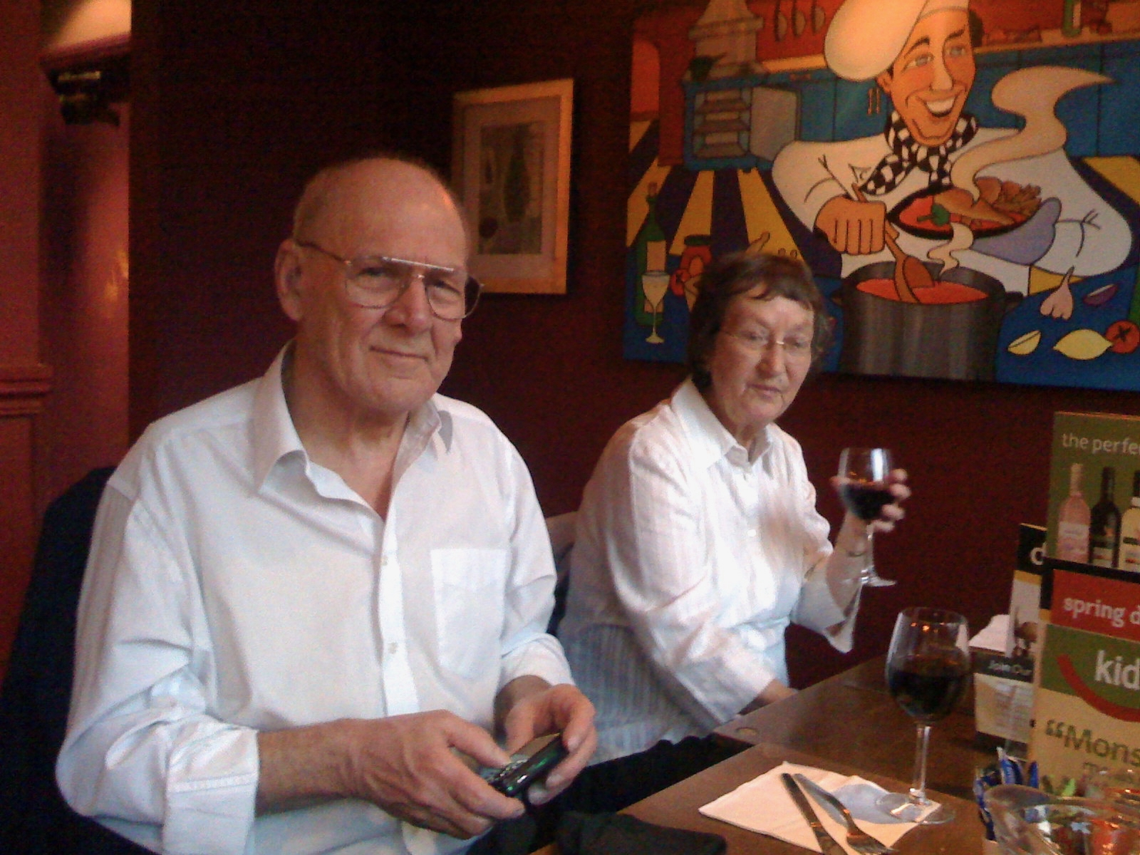 BPhotograph of the autho's parents, sat at a meal table, father with a camera, mother with a glass of wine