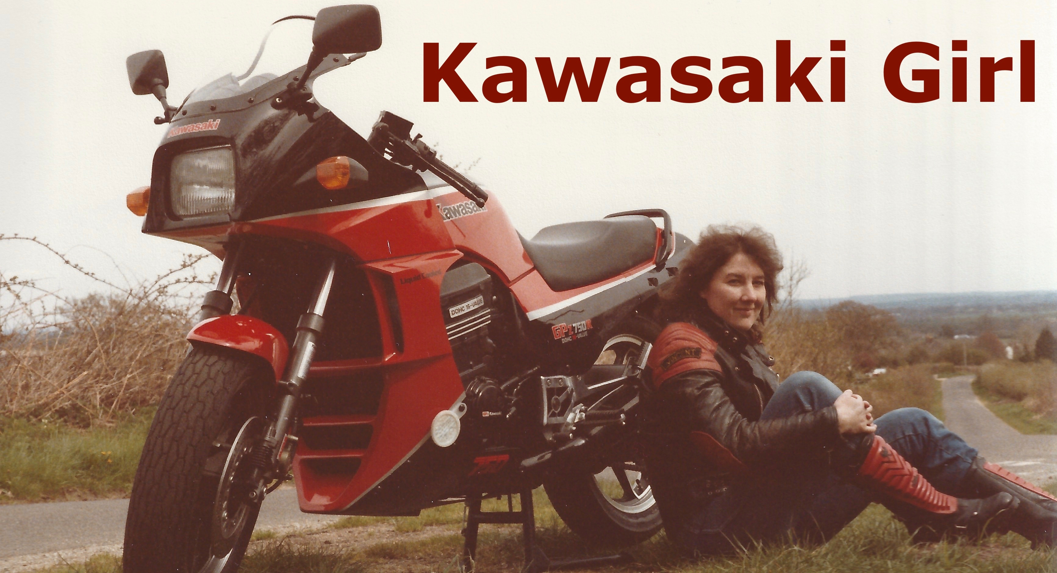 The title card showing a still from the video Kawasaki Girl showing a red and black Kawasaki GPz750R on its side stand on a grassy bank at the top of a hill with a leather jacketed clad, dark haired woman in blue jeans and wearing red and black motorcycle boots sat against the side with matching red title graphics.