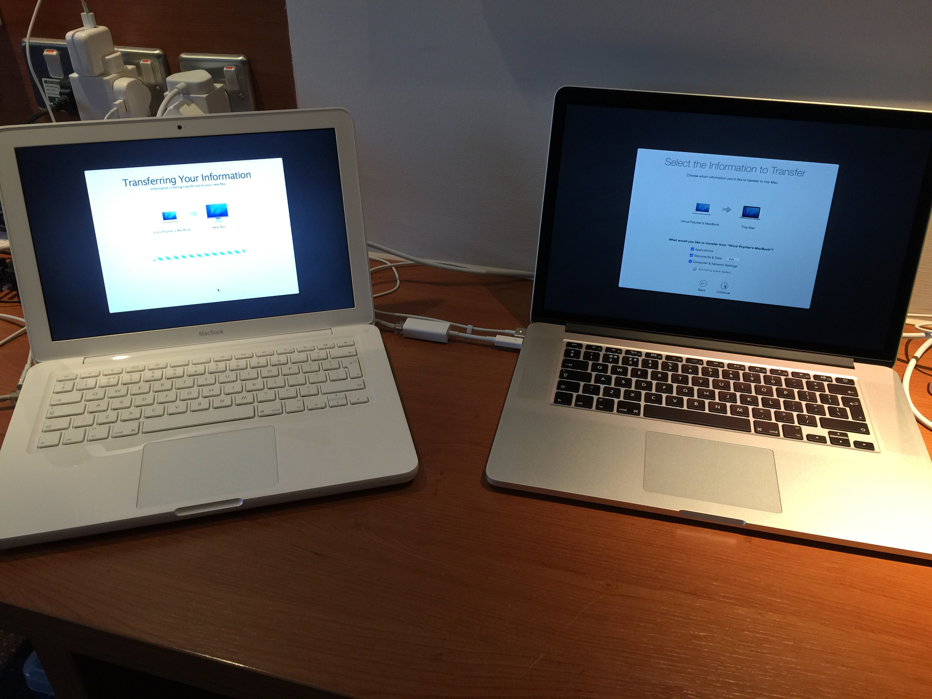 Two MacBooks side by side interconnected on a wooden desk top, linked by cables and connected to a heavily used pair of wall sockets. The white plastic, unibody MacBook on the left shows an operations window stating 'Transferring your information' and the silver MacBook Pro on the right shows an operations window stating Select the information to transfer'.