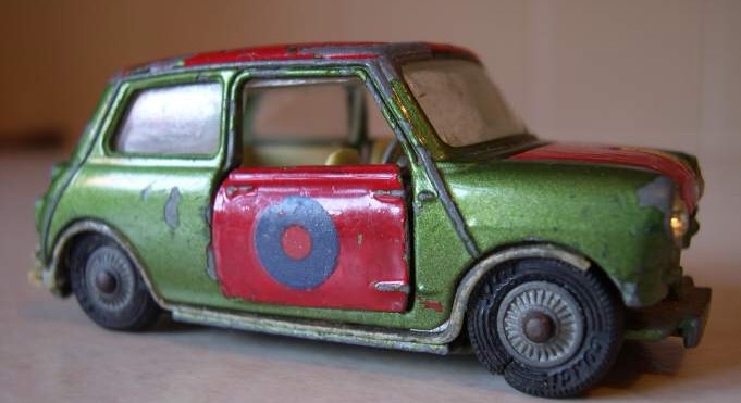 A rather battered green two door Corgi Toy Mini with red hand painted door, roof and bonnet. A large blue 'o' is on the door, the suspension is collapsing and the tyres and trim are damaged