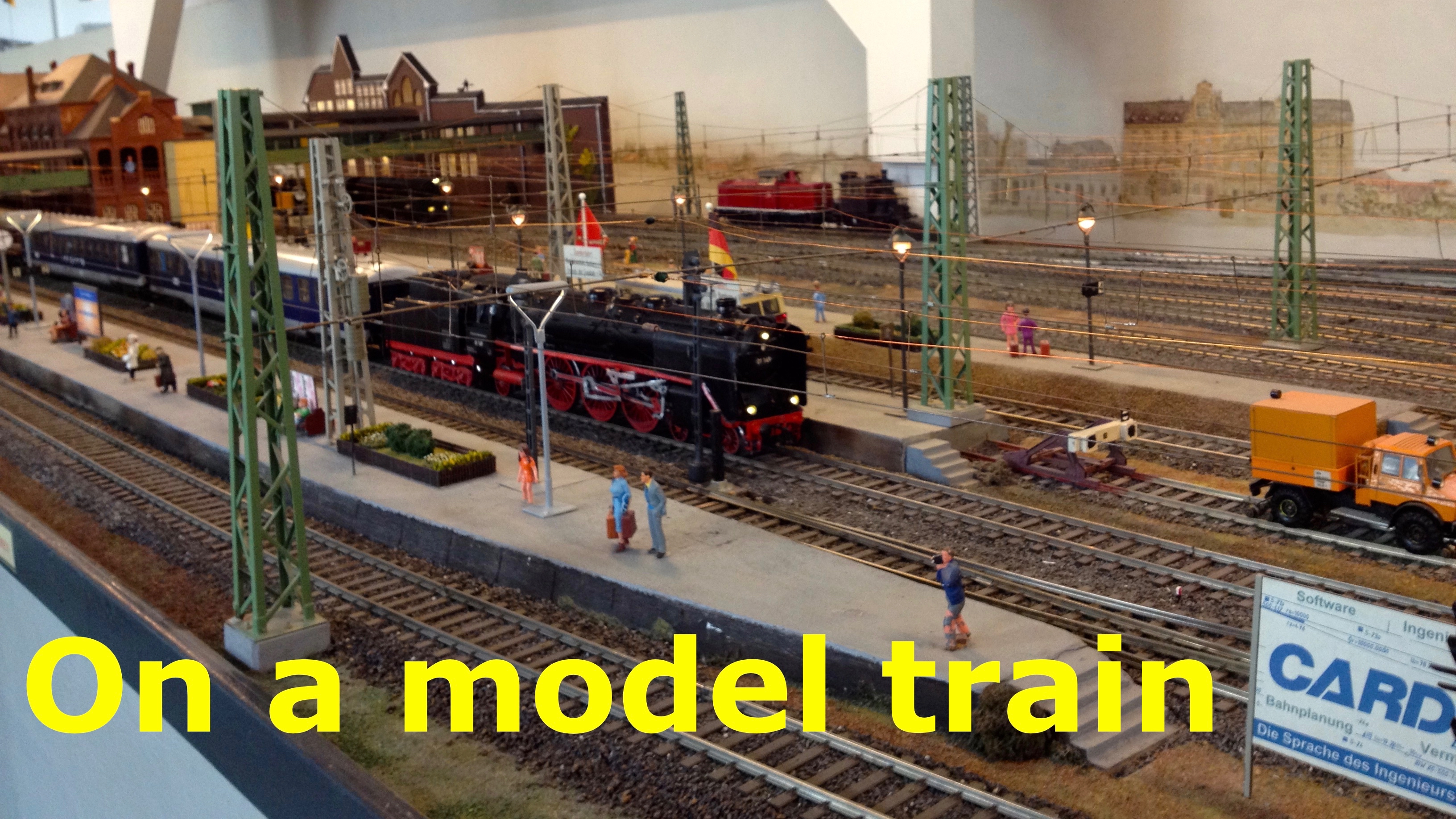 The title card from my short video showing a model rail diorama with a multi track layout showing a black classic steam engine and carriages passing through a station where some figurines are waiting on a platform with the title On a Model Train