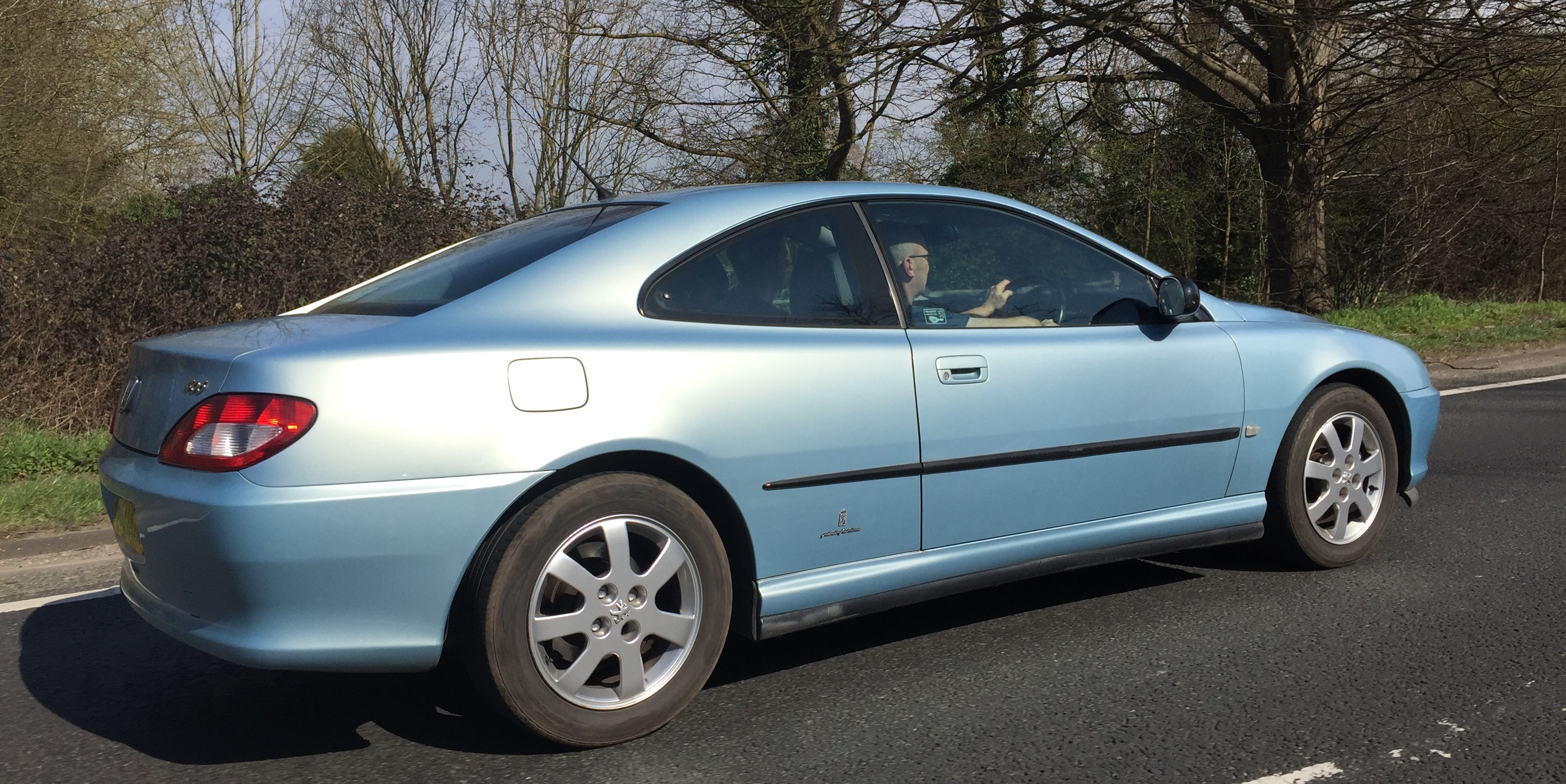 Image of a light blue Peugeot 406 coupe travelling on a road