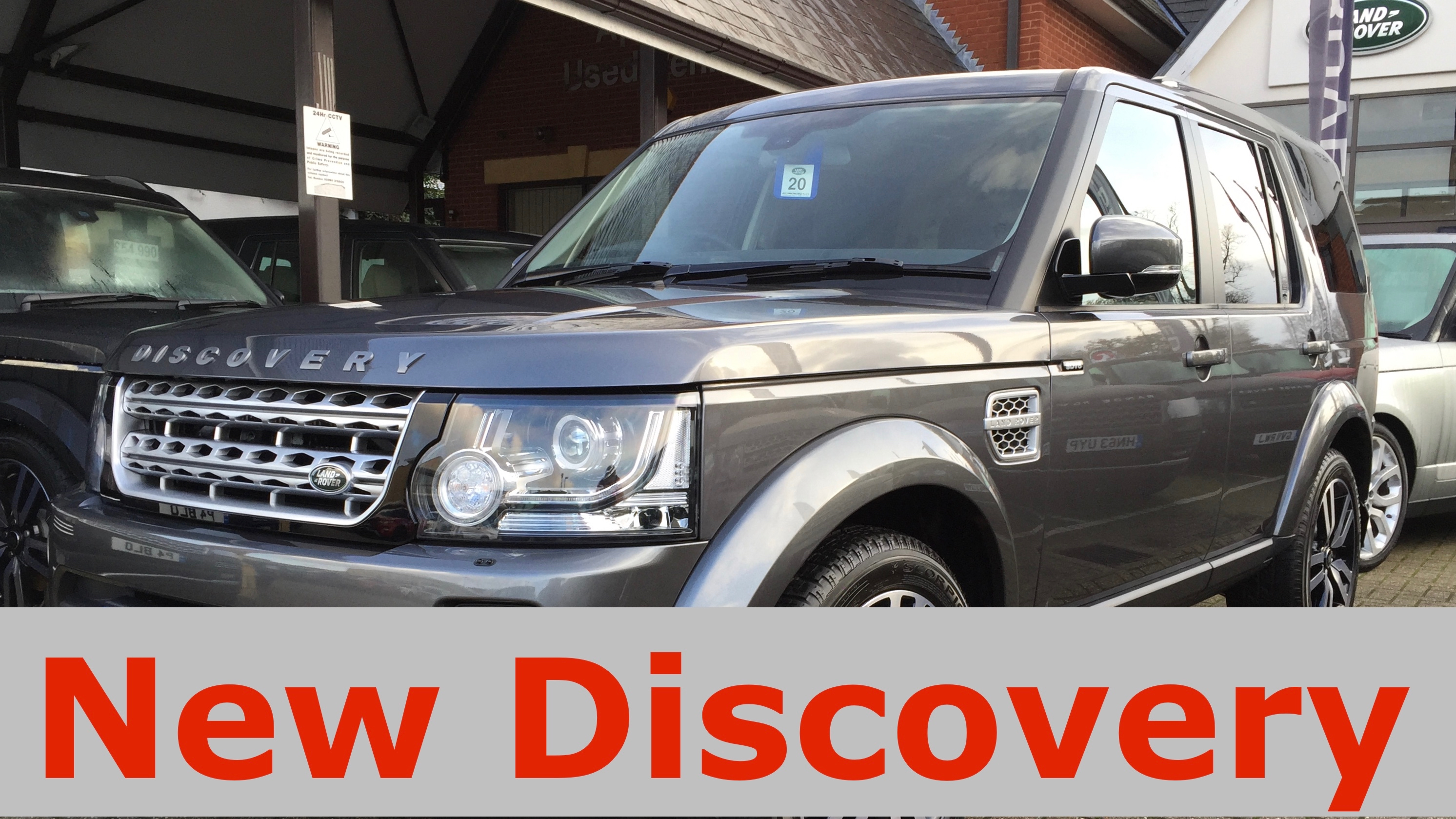 Image of a new grey Land Rover Discovery parked outside a Land Rover dealership with a Red on grey text lower third stating New Discovery