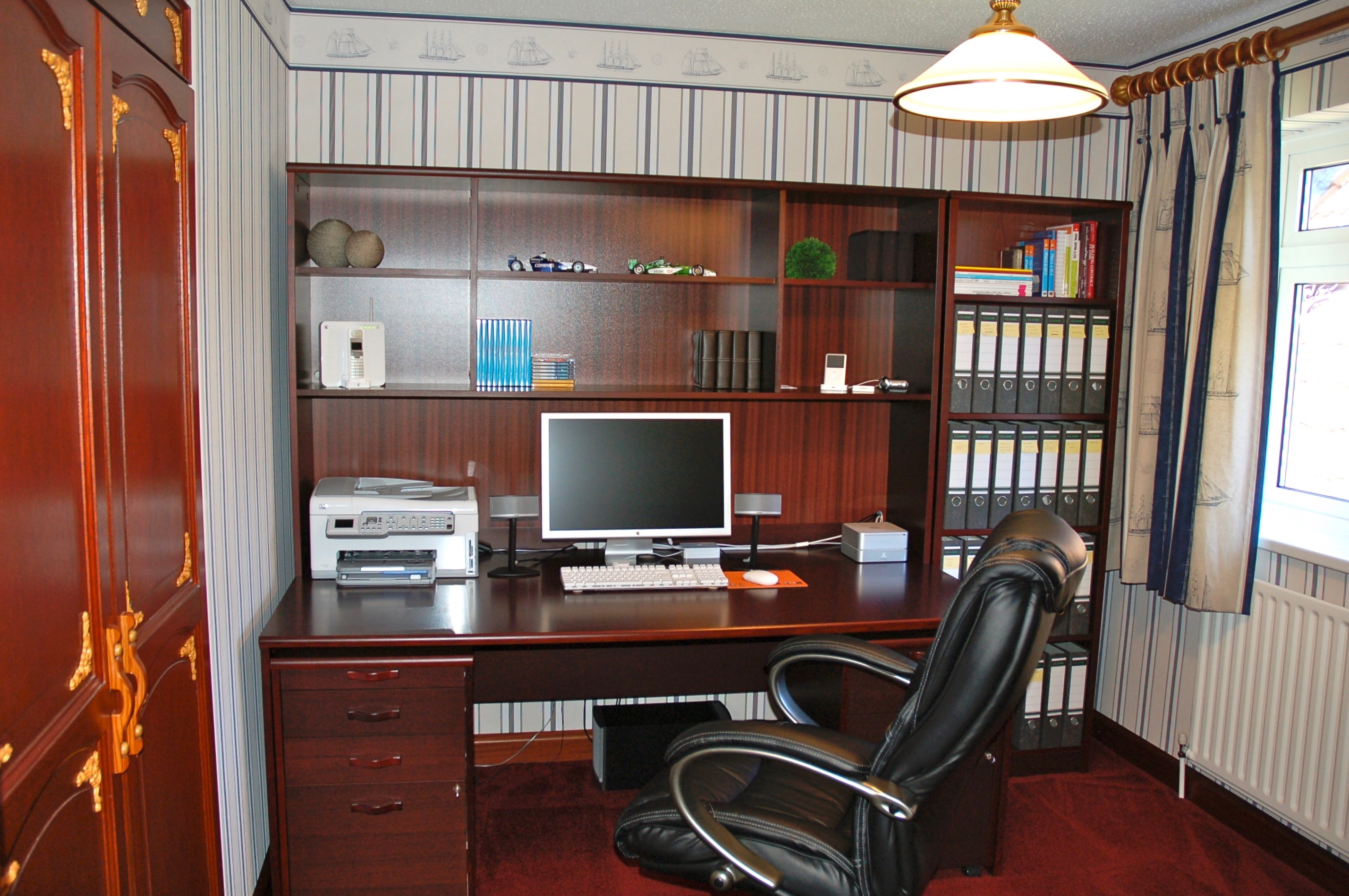 The author's spare bedroom converted to a nice office set up. The matching wallpaper and curtains, the dark wood office style furniture complimenting the wardrobe doors, the black leather executive swivel chair and the neat rows of lever arch file boxes. The computer set up is dominated by the 23 inch Apple Cinema display, with a MacMini on top of a matching back-up drive sat to the right and a Hewlett Packard all-in-one printer to the left. Also seen is an optical mouse, small stereo speakers, an iPod Classic a BT Homehub and an underdesk bass sub-woofer