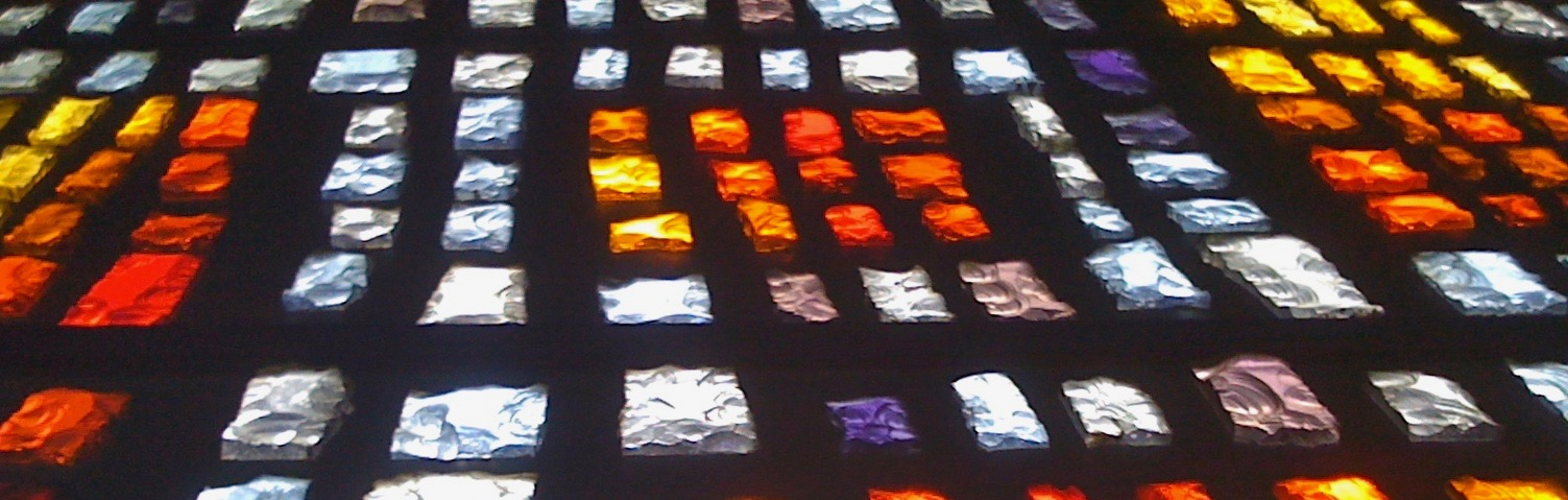 A photograph of an old cathedral glass window design comprising multiole coloured rectangles