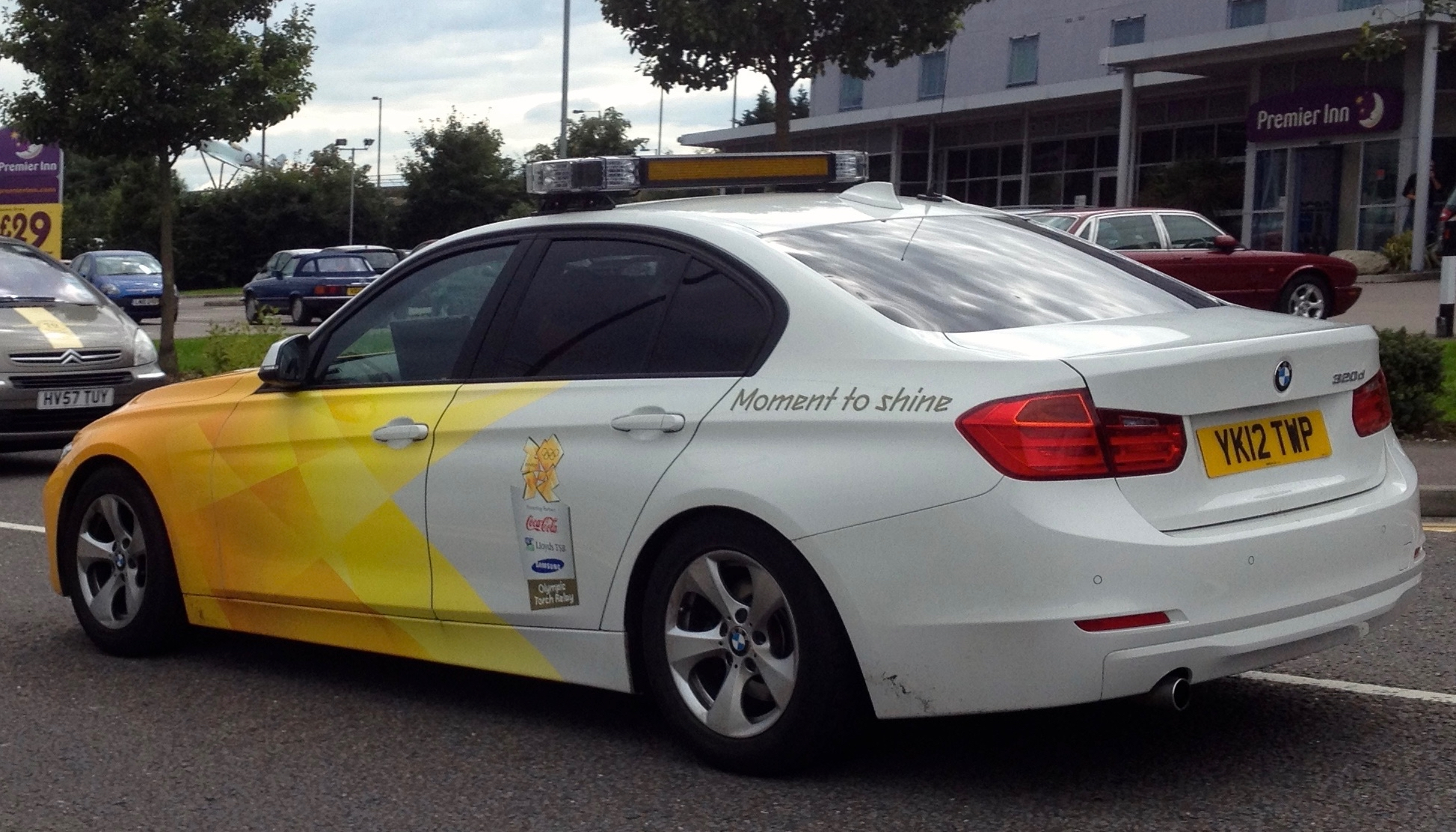 A BMW 3-series 320d painted in the orange, yellow and white Olympic branding