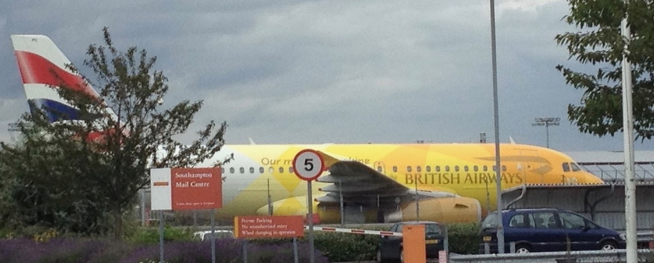 An aeroplane awaiting passengers painted in the orange, yellow and white Olympic branding