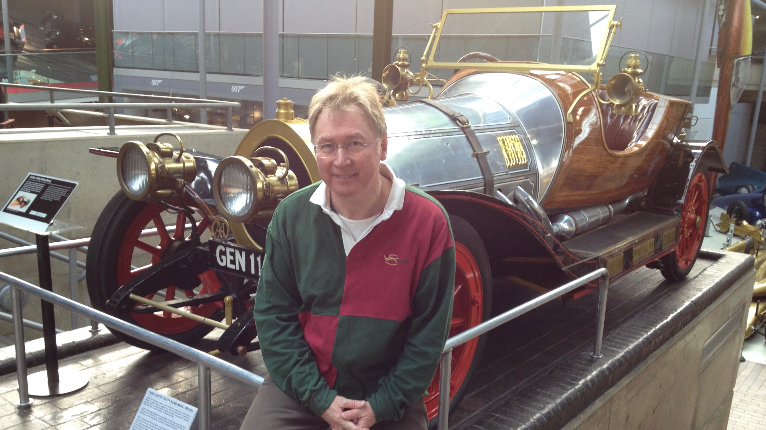 A photograpgh of Vince sat against the railings surrounding the Chitty, Chitty, Bang, Bang car at the National Motor Museum at Beaulieu