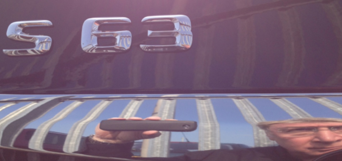 A close up selfie style photograph of the rear end of a shiny black Mercedes-Benz S Class with the chrome S63 badge showing and a distorted reflection of the author showing up in the chromed boot line holding his iPhone camera.