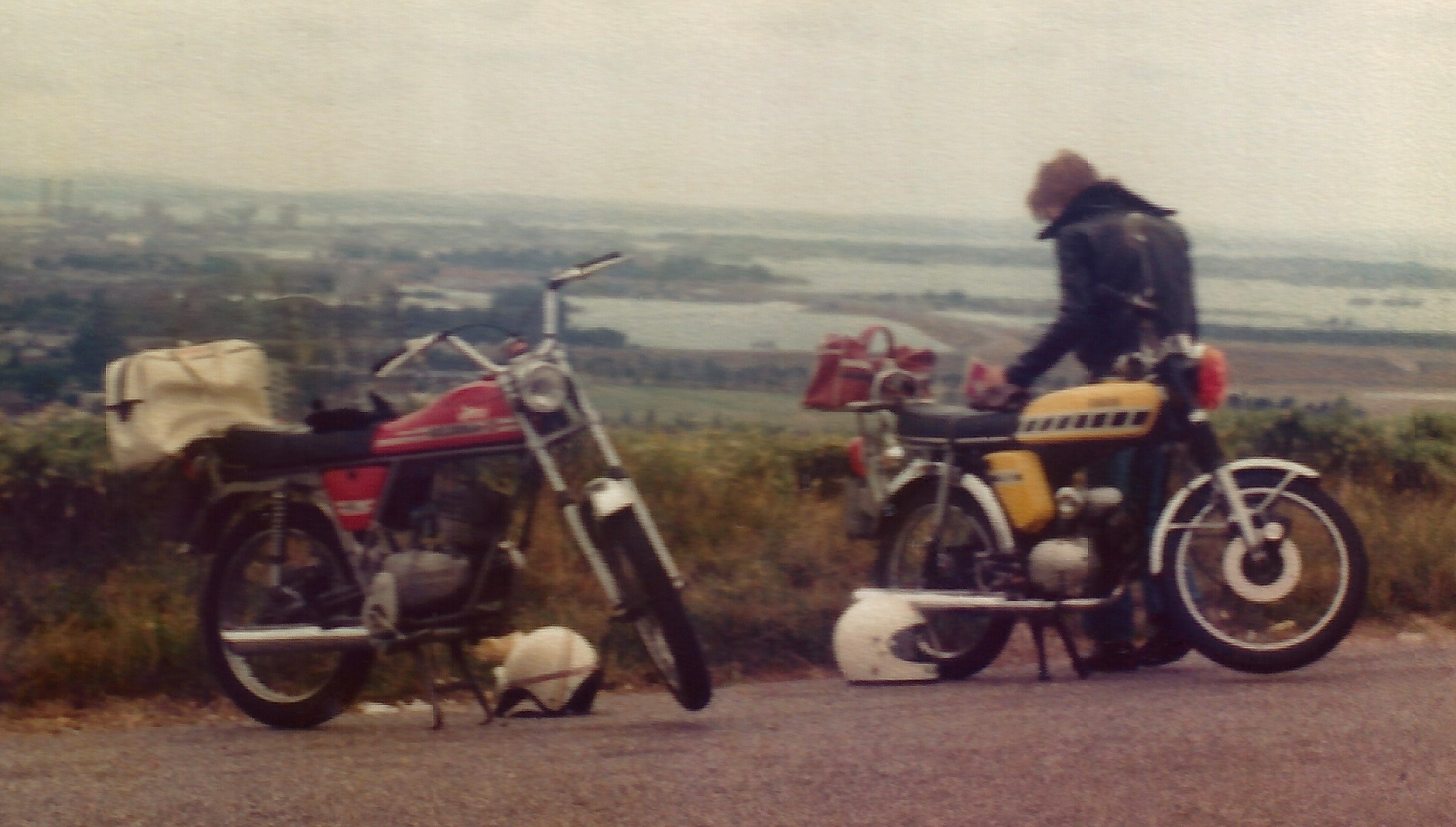 Two mopeds are parked overlooking a large coastal town.  A red Gilera 50 Touring moped on the left and a yellow Yamaha FS1E have luggage backs packed on the rear. A leather jacketed rider is checking out something on the seat of the Yamaha