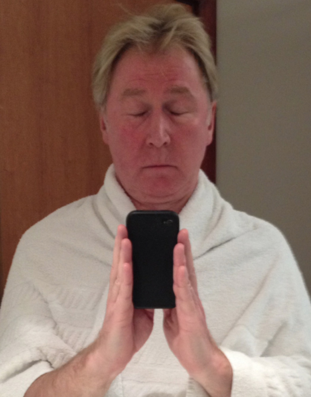 A selfie by the author taken in a bathroom mirror.  He stands holding the iPhone camera as if his hands are praying.  A white towel draps across his shoulders and his eyes are shut in contemplation