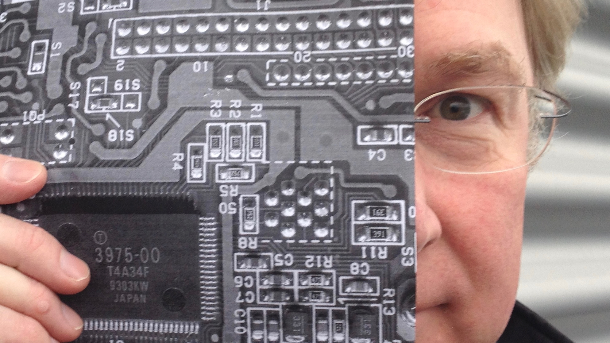 A selfie style photograph of the author with his face half covered by a black and white paper print of a close up circuit board.