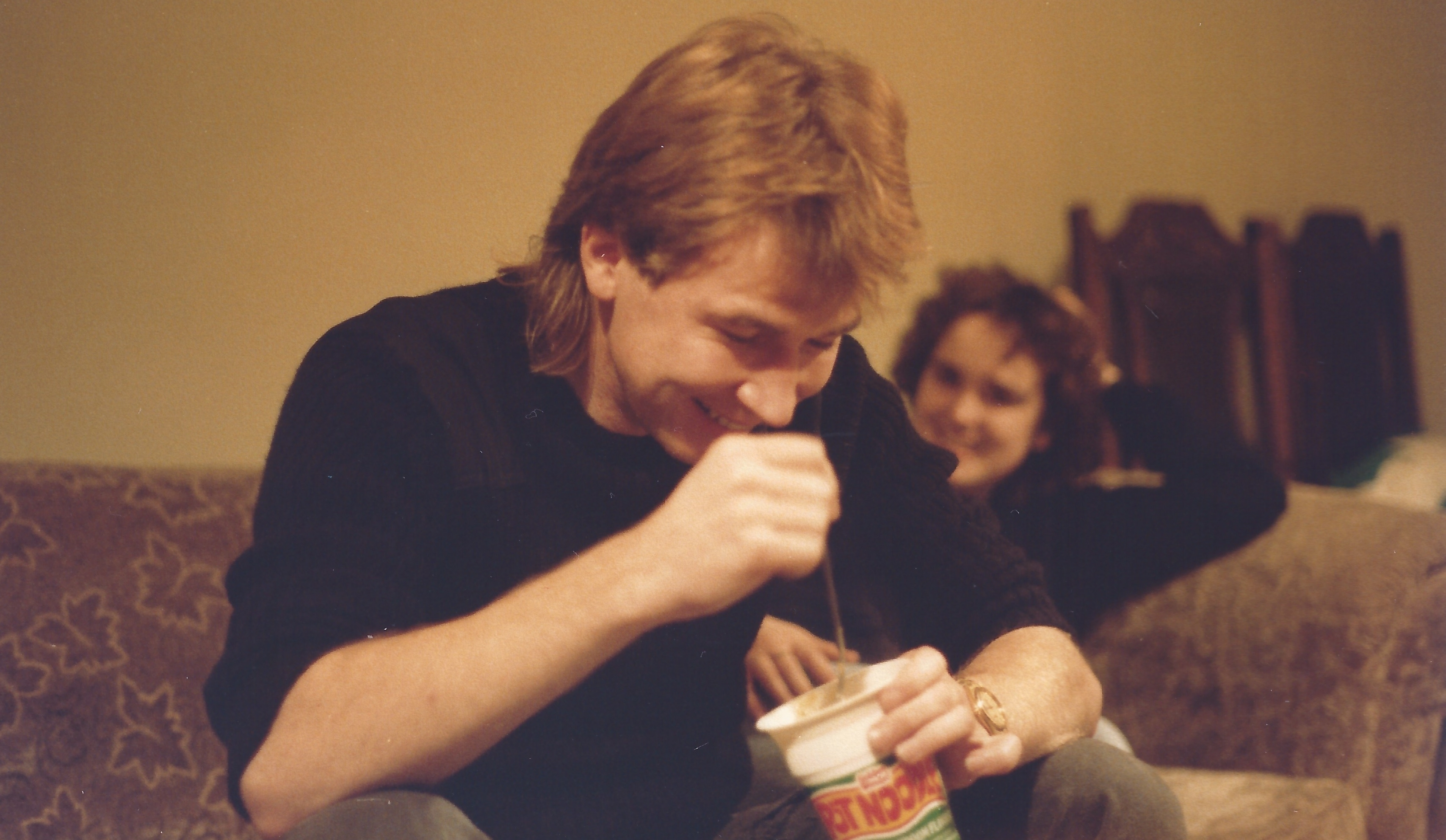 Vince Poynter sat, tucking in to a Pot Noodle, with a female friend in the background