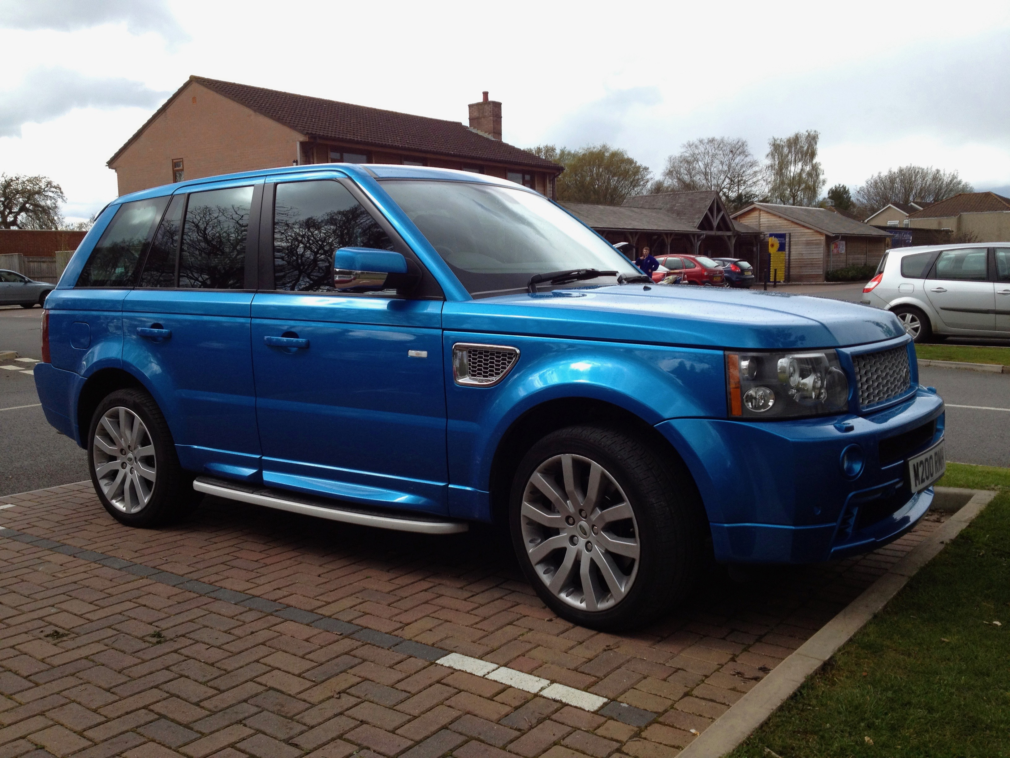 Image of a blue Range Rover with black out side windows
