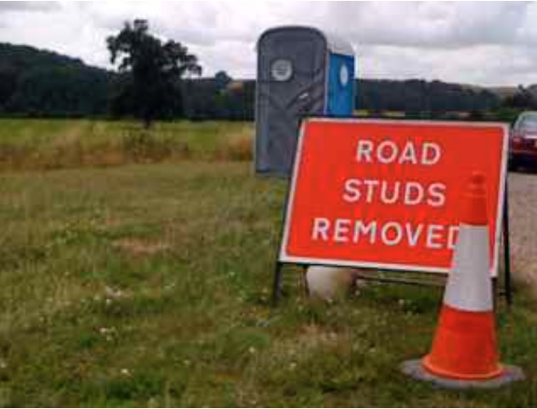 A self supporting temporary roadsign erected at the side of the road with white lettering on a red background reading - Road Studs Removed