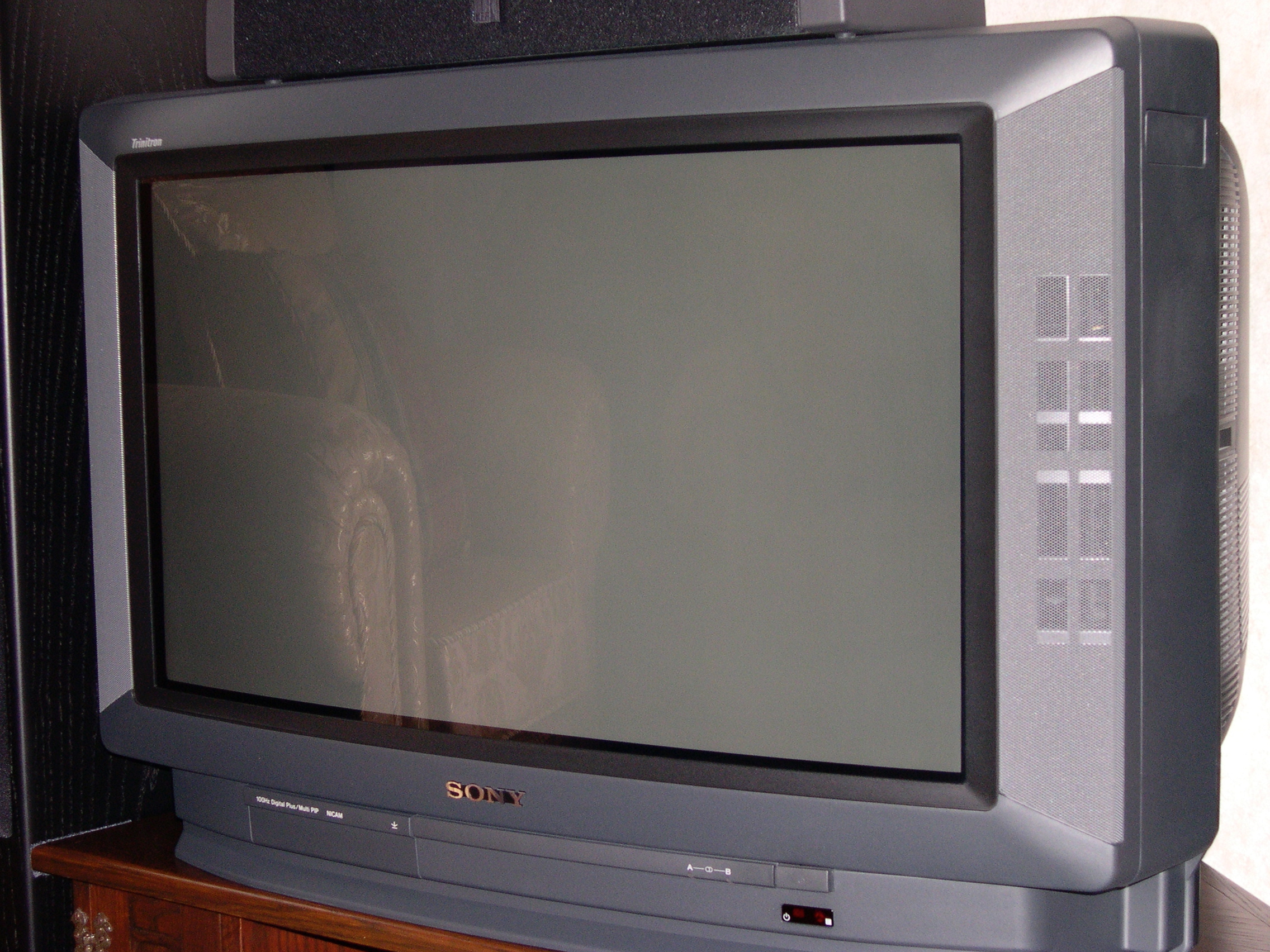 A large, grey Sony Trinitron CRT television sat on a dark wood TV corner stand unit