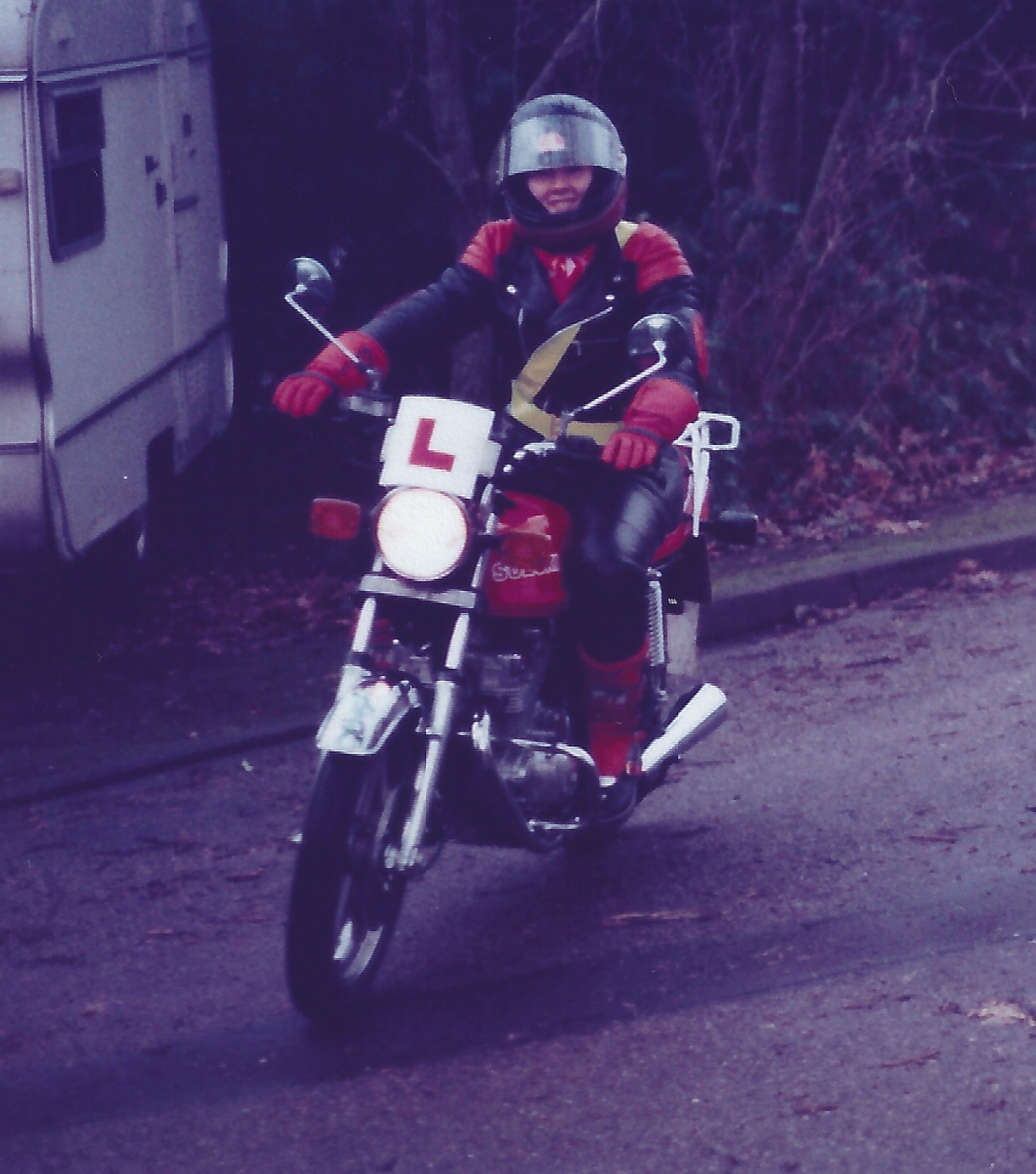 A front three quarters view of Lynda Poynter, riding her red Suzuki GSX250 around a tight roundabout with a partially obscured caravan in the background. Lynda is wearing all her matching motorcycle protective clothing including black and red leather jacket, black leather trousers and black and red moto-cross style boots and a fluorescent yellow body sash