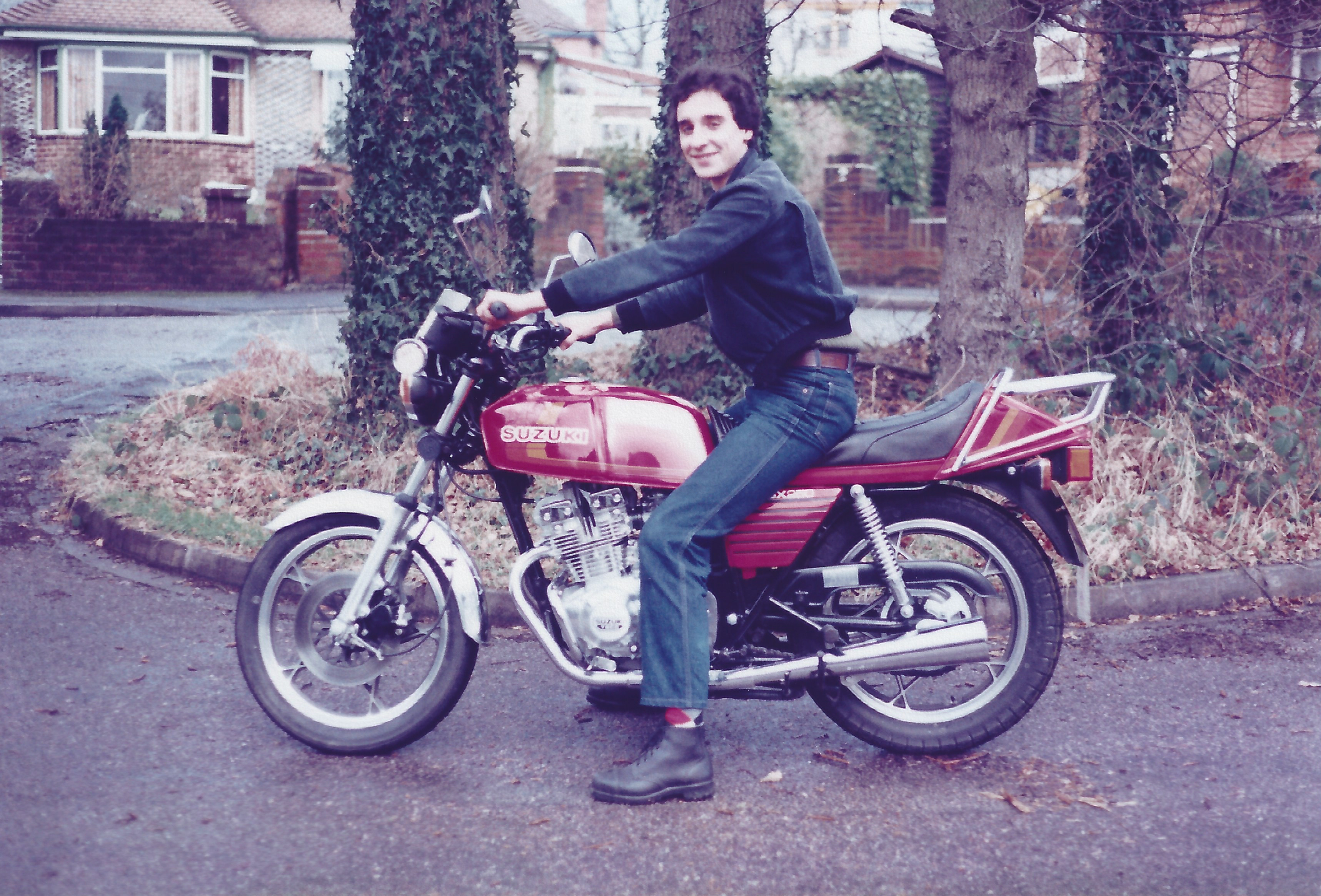 A side view of Kevin Clare, wearing blue jeans, a lightweight grey jacket and utility style boots sitting on Lynda's shiny, new, red Suzuki GSX250. The rear chromed luggage rack is shown along with a clear view of the side panel which has several parallel black stripe indentations. The bike is positioned on a small, quiet residential, roundabout with four large trees on it