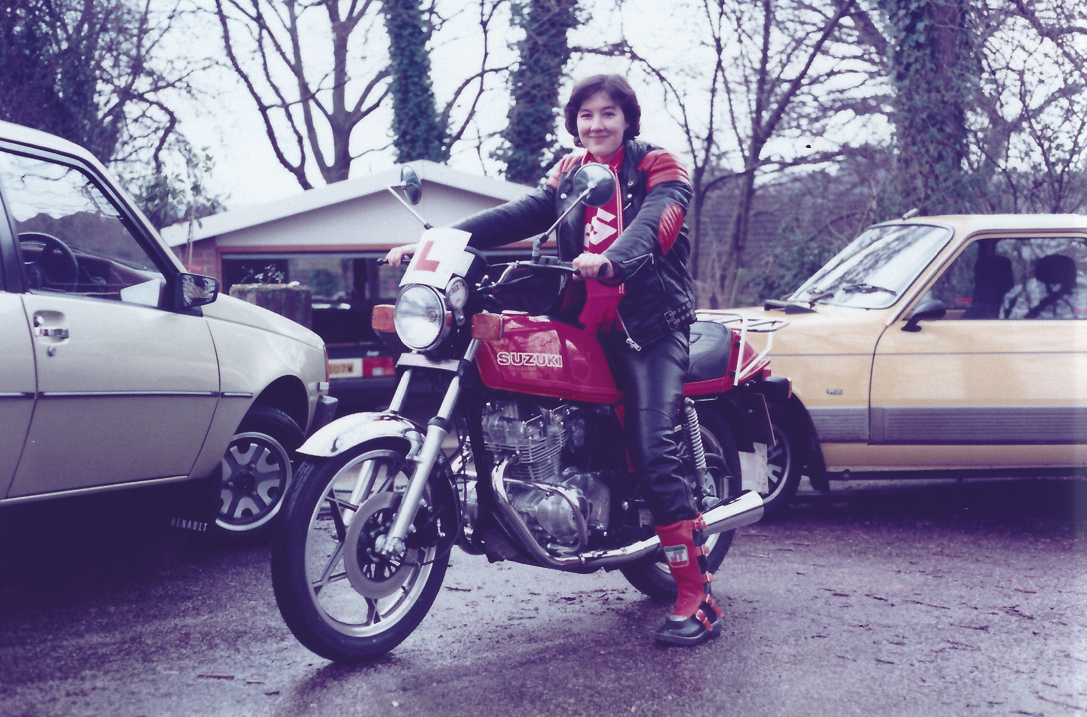 A front three quarters view of Lynda Poynter, helmetless and wearing a black and red leather jacket, black leather trousers and black and red moto-cross style boots sits on her shiny, new, red Suzuki GSX250 which sports a high level mounted L Plate.  Three Renault cars are in the background including a Renault Fuego in the garage
