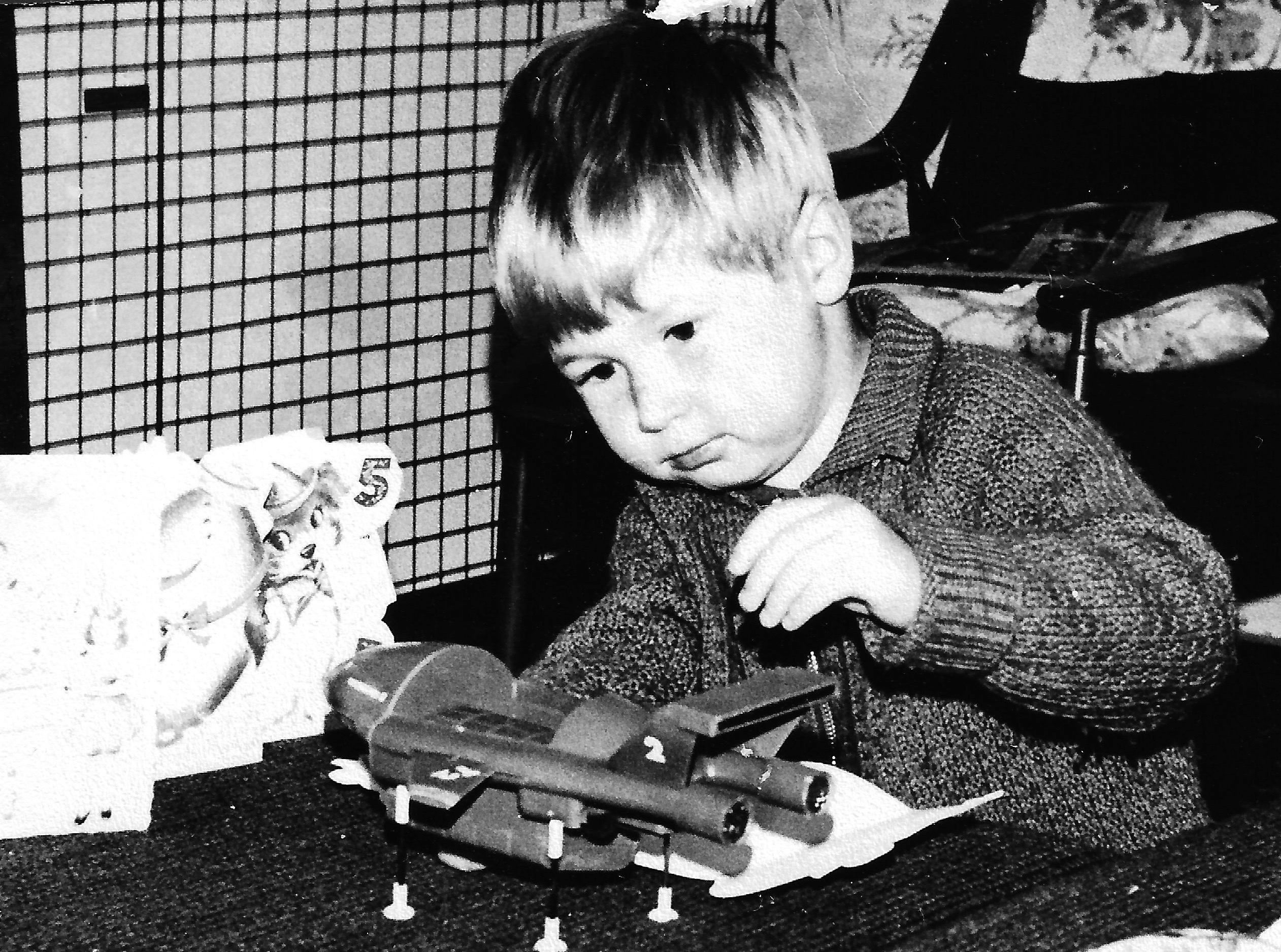 Black & white photo of Vince playing with a Thunderbird 2 model