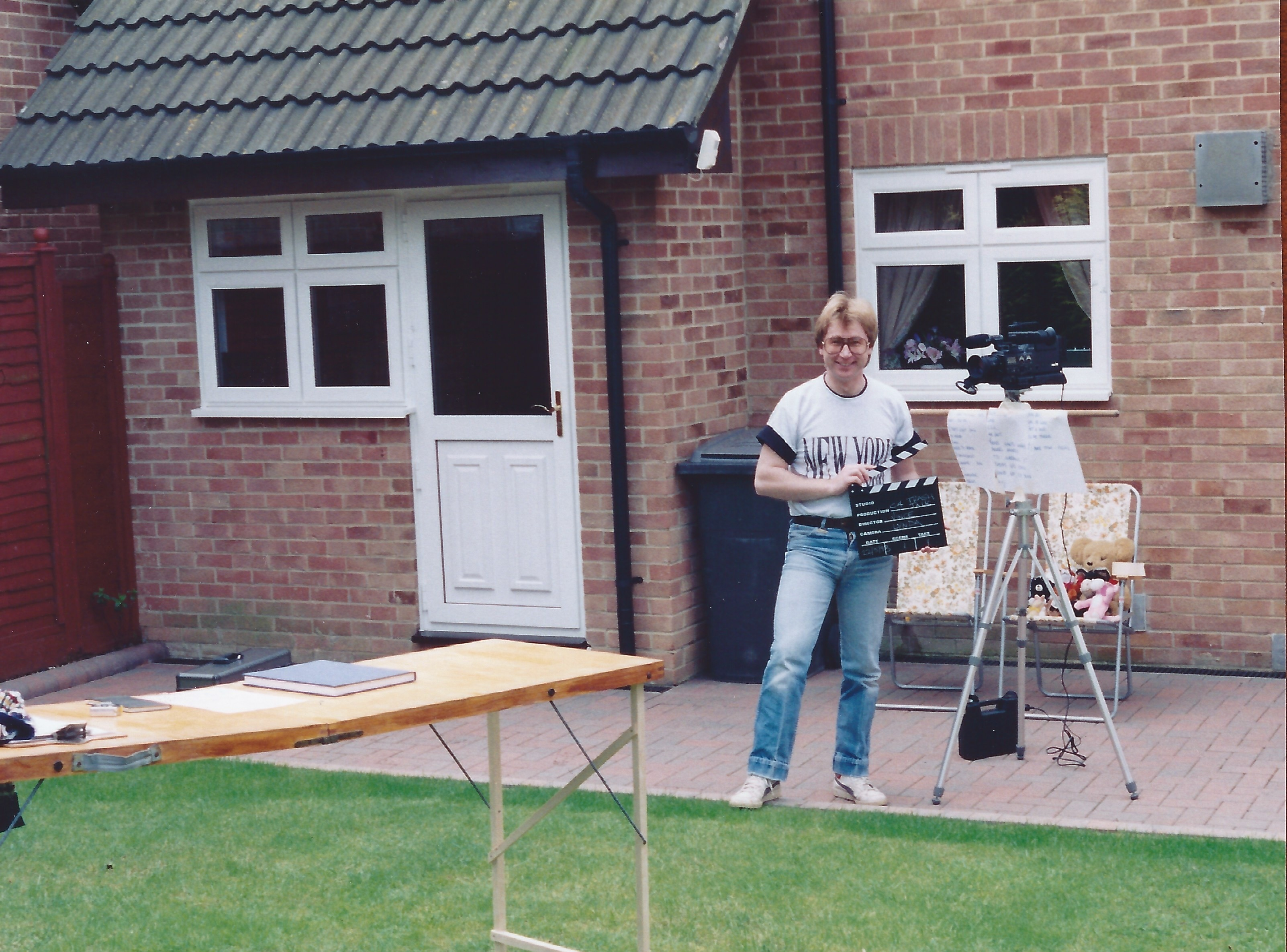 Image of the author in his back garden holding a clapperboard, next to a tripod mounted classic shoulder mount camcorder, next to a wallpaper table on which is a clipboard a book.  In the background two deck chairs and some soft toys