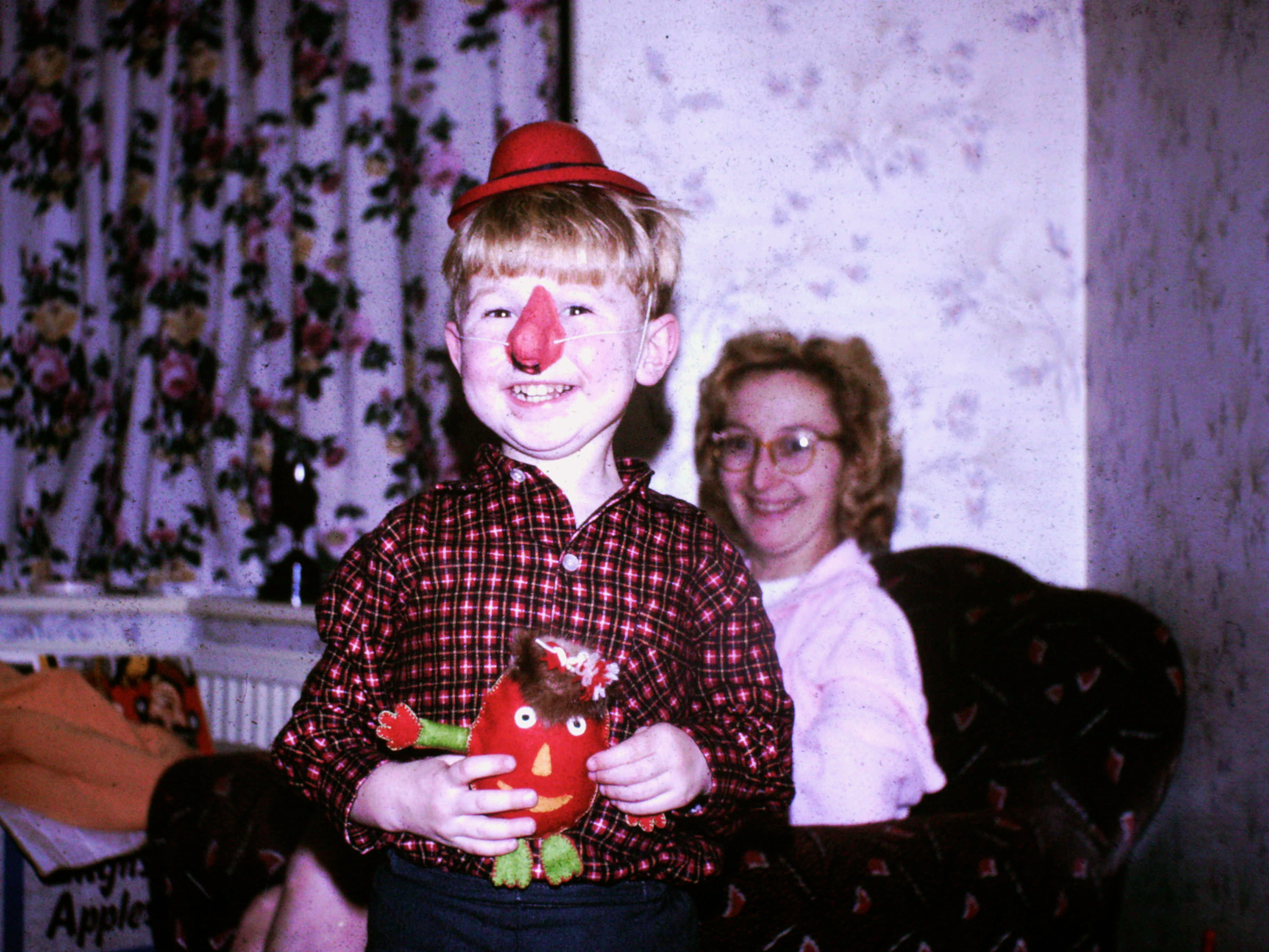 Image of Vince Poynter stood, wearing a small hat and large red nose, holding a gonk, with Lilian Poynter sat in the background