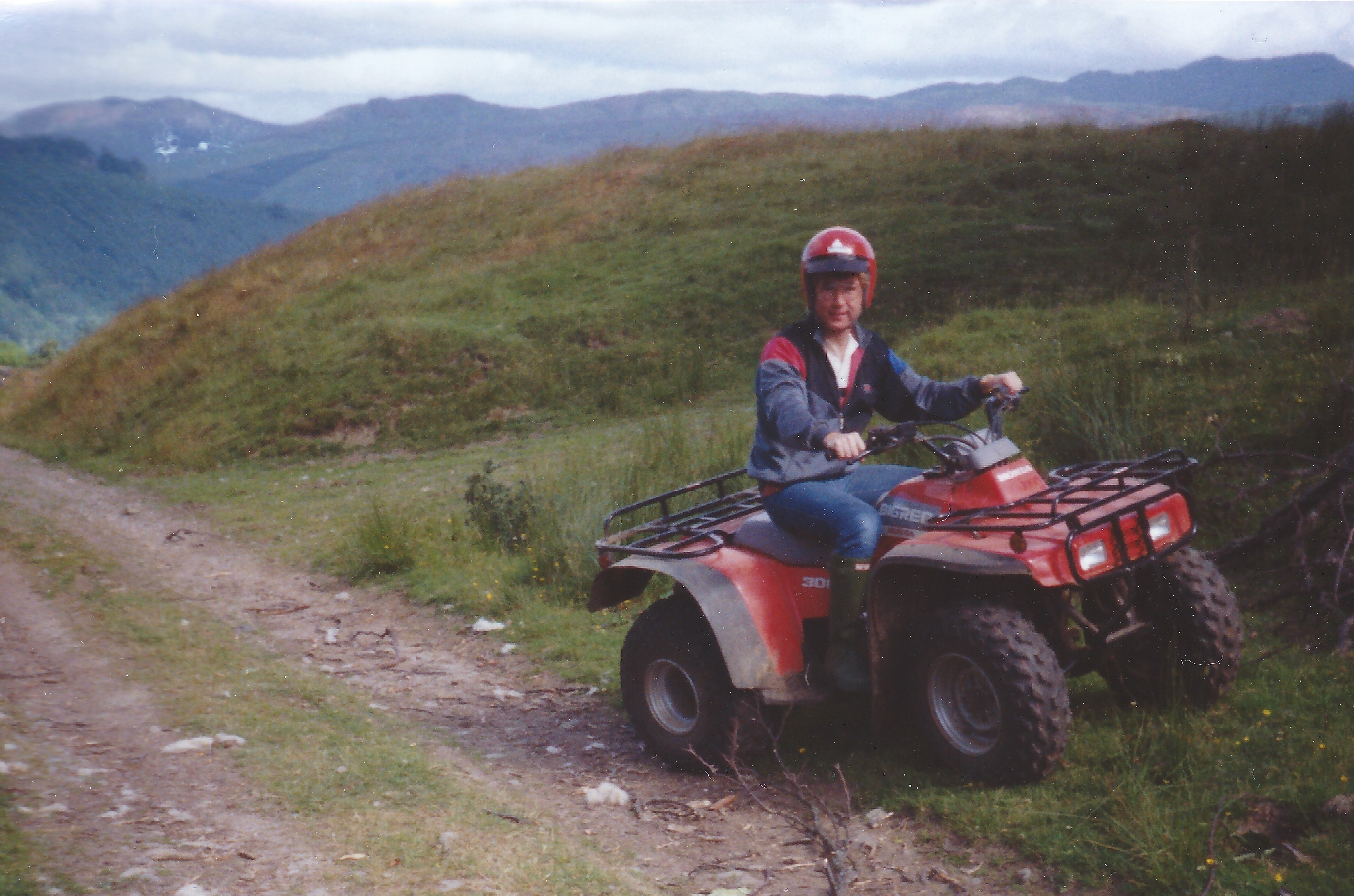 The author sat on a red Honda 300 quad bike high in rolling grass covered hills in the Welsh countryside. The bike is parked just off a dusty dirt track headed to a small pass. Vince is wearing a grey shell style suit top and blue jeans, green Hunter Wellingtons and a red open faced helmet with black peak