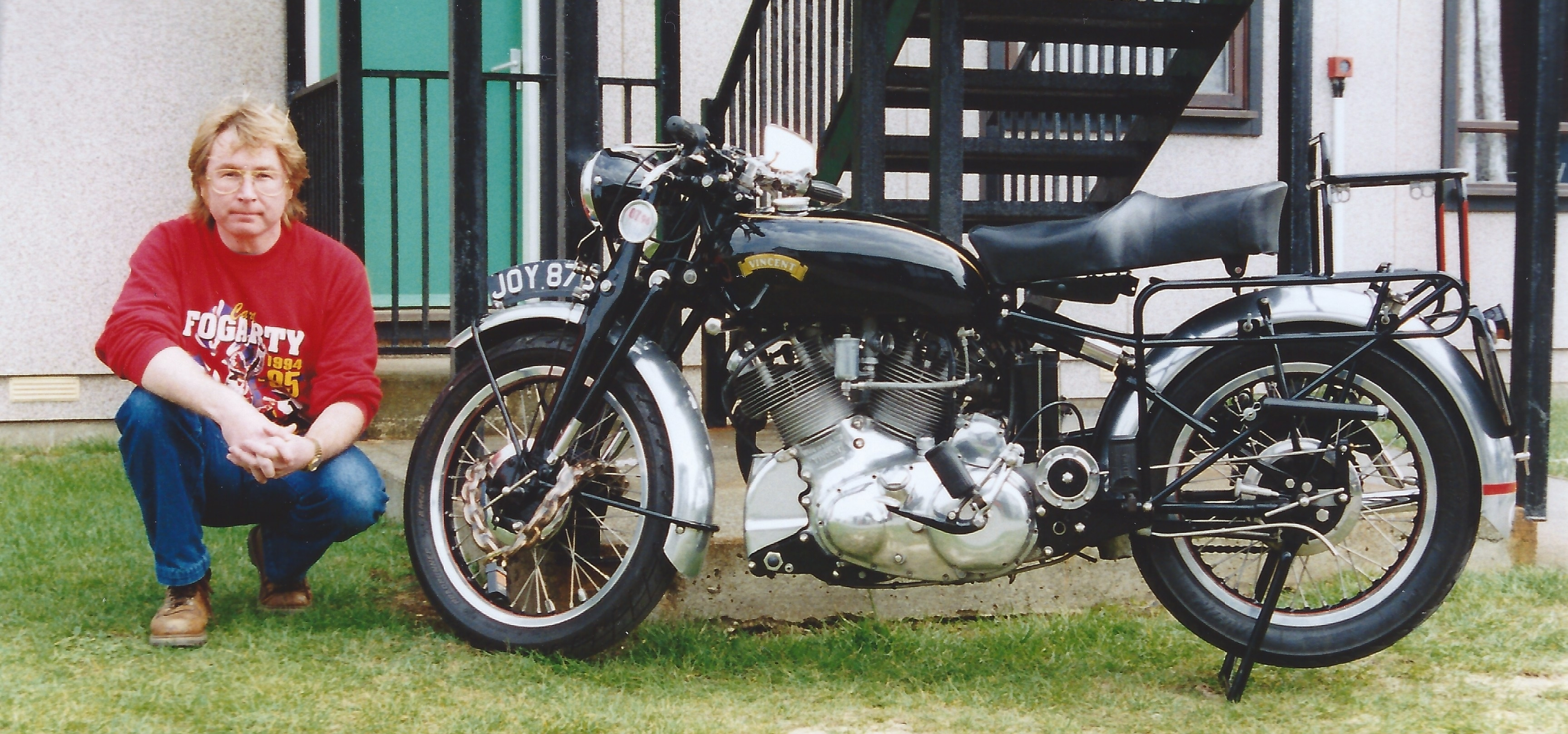 A photograph of Vince squatting next to a Vincent Rapide motorcycle